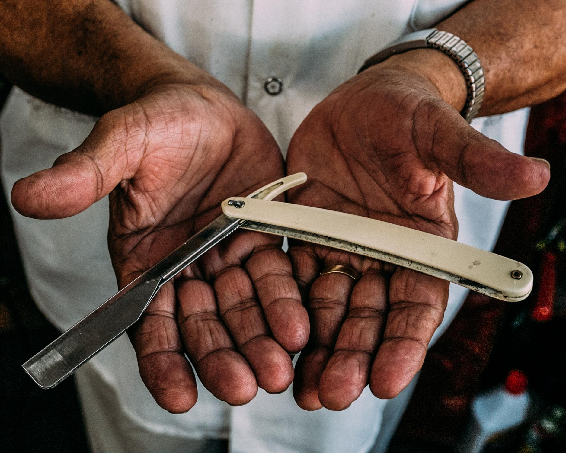 "Standing in the barbershop he founded four decades prior, Eladio Burgos, 77, displays one of his straight razors at his barbershop, on Suydam Street and Wyckoff Avenue, as he tells tales of the blocks ""wild west"" days."