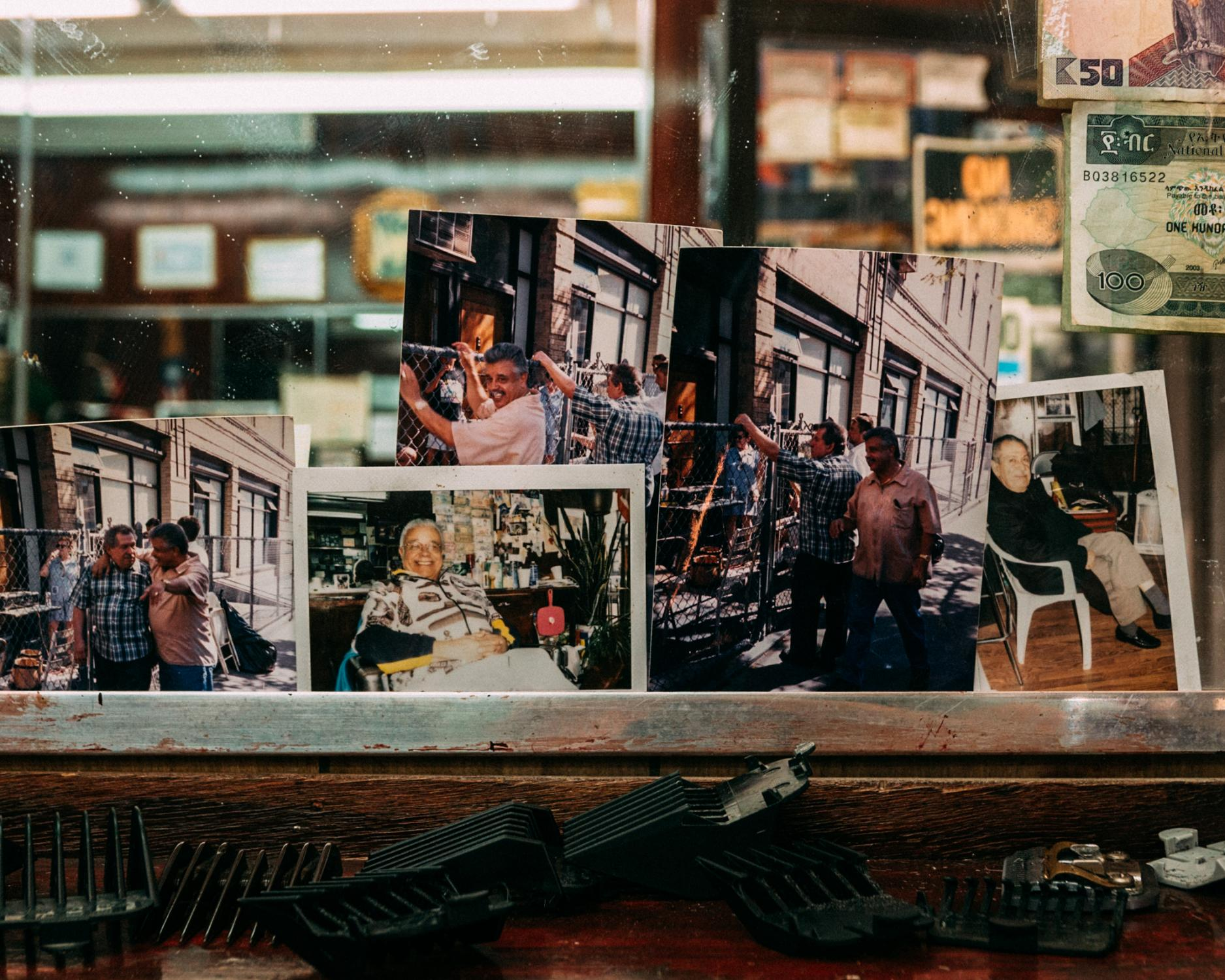 Photographs displaying moments from the barbershop's earlier years hang above a shelf inside the barbershop created out of a small garage on Suydam Avenue in the Bushwick neighborhood of Brooklyn.