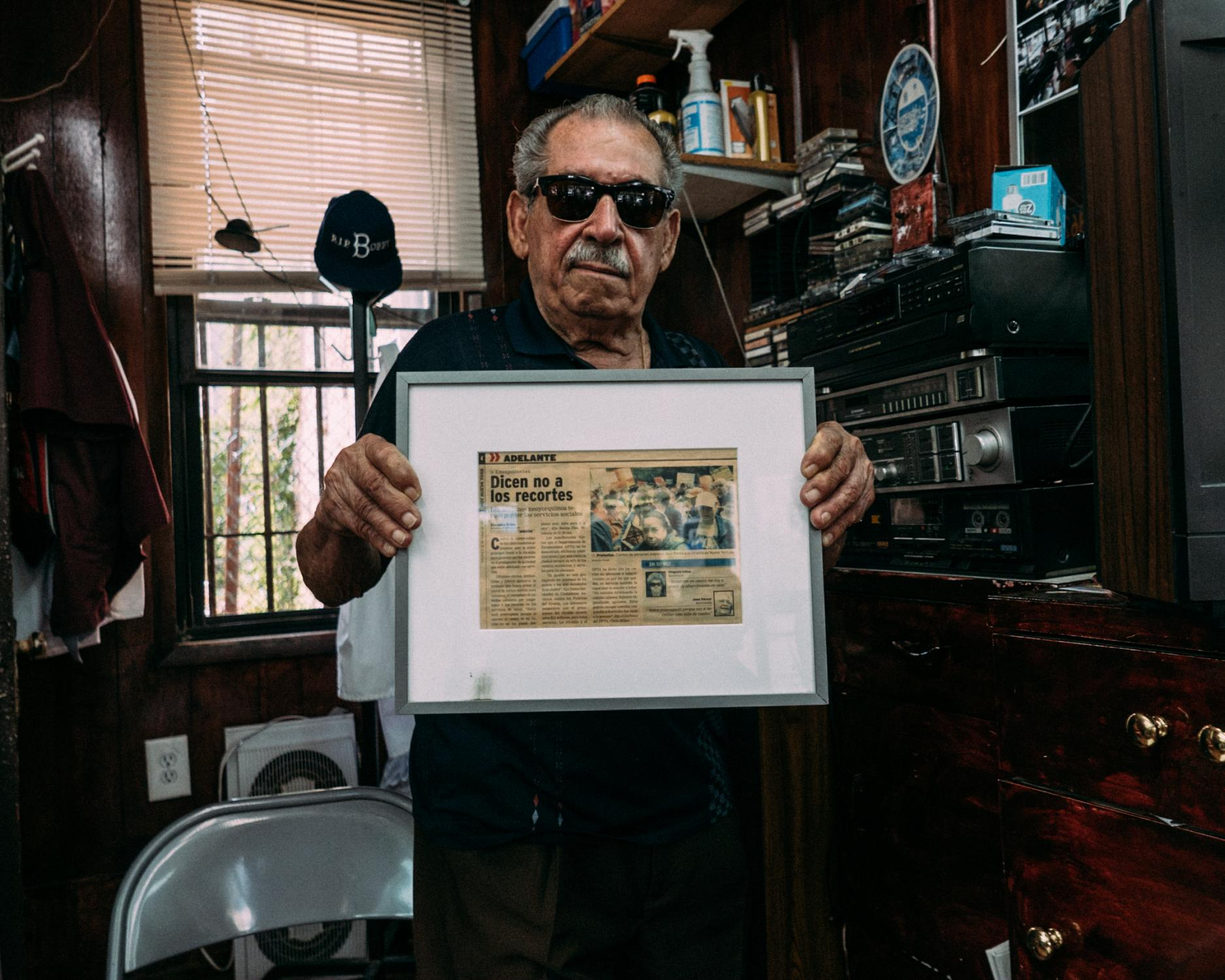 A long time friend of Eladio proudly presents an article by Alexandra Ochoa originally printed in the Latino publication Hoy Nueva York that displays a photograph featuring Eladio fighting for social services for elderly New Yorkers.