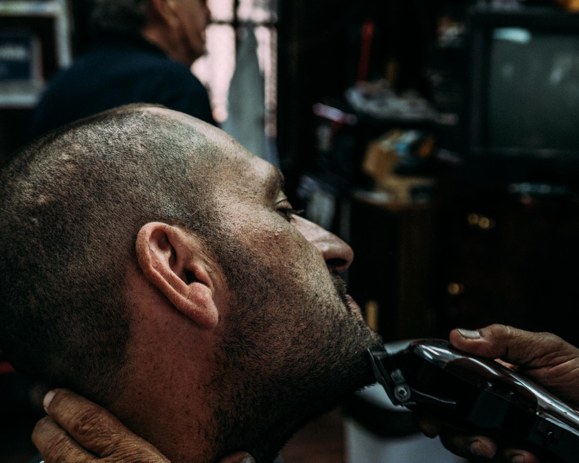 """The shop is open from 9 am to 6 pm sharp, except summer nights. During the warmer months, Eladio and old friends spend time playing dominoes and listening to traditional Puerto Rican music in-between haircuts. Here, Eladio finishes up the final hair cut of the night before starting """"la janguear"""" (the hang out)."""
