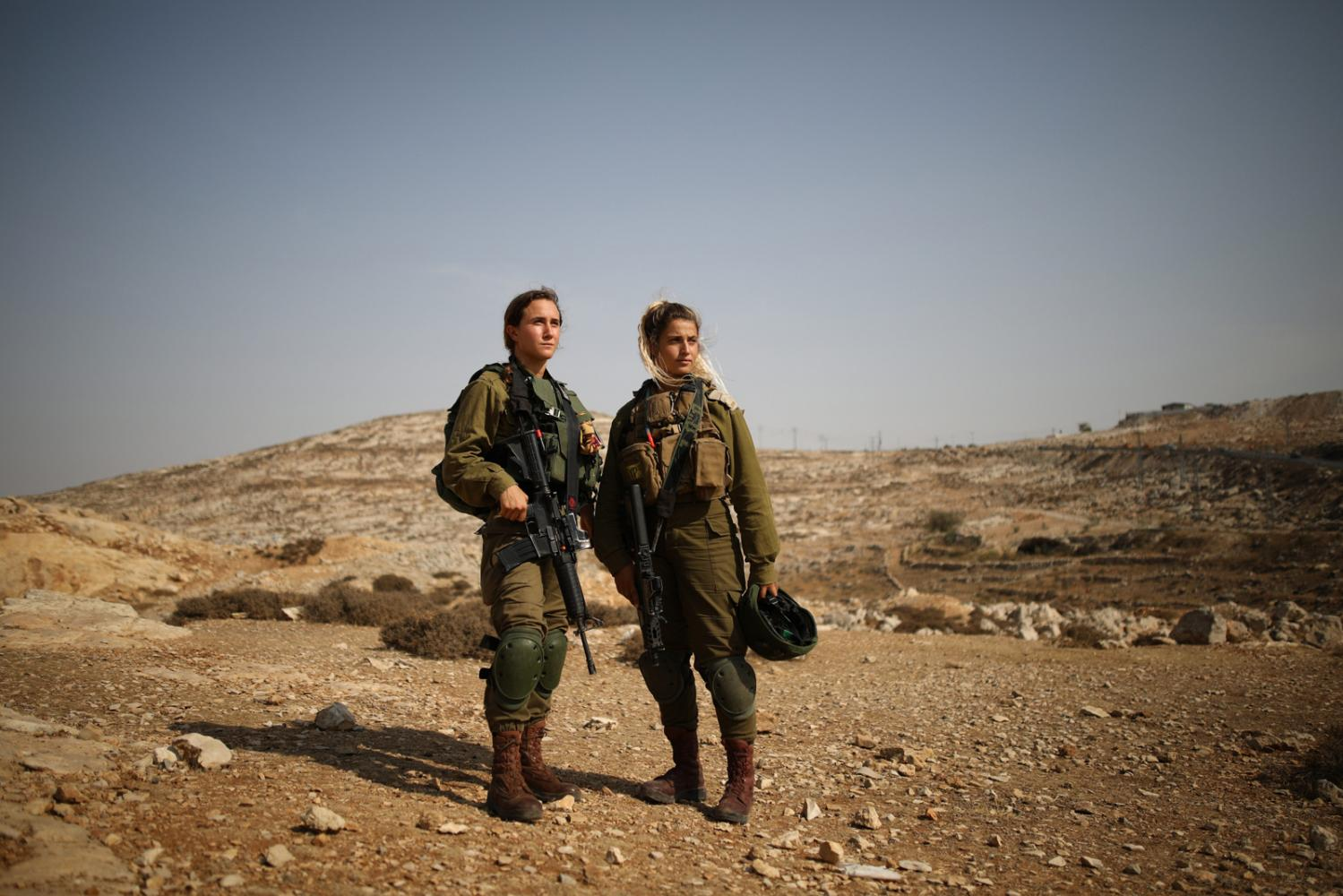 HIZMA, WEST BANK - OCTOBER 03, 2018: Portrait of Libby Zelikowitz (left), 23, 'lone soldier' from New York, and of Yaar Perlow (right), 21, Platoon commander, both soldiers of the Caracal Battalion, a mixed-gender infantry combat battalion of the IDF, near the Palestinian villages of Hizma and Atarot, West Bank. CREDIT: Corinna Kern for The New York Times