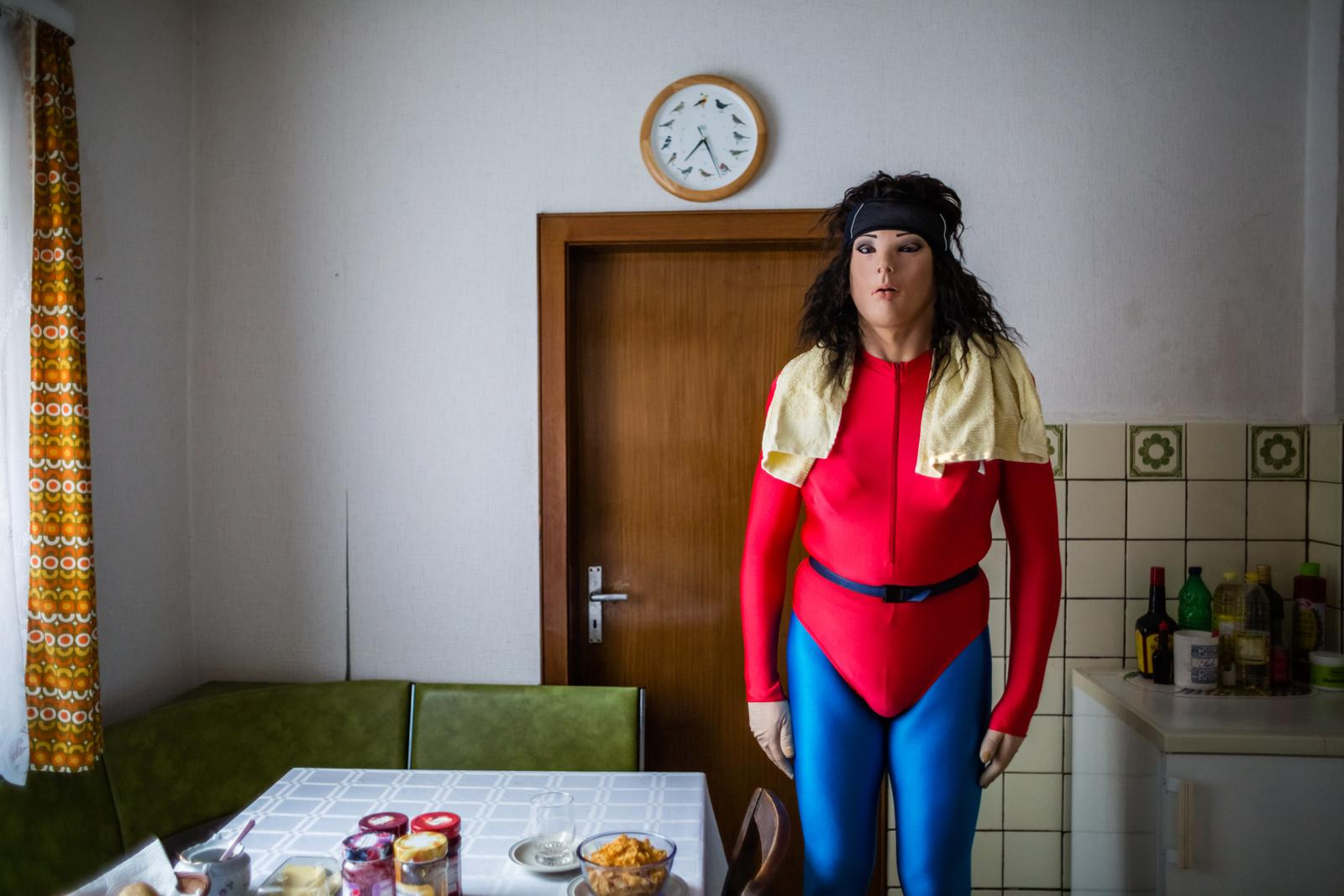 """HANNOVER, GERMANY - AUGUST 23, 2015: Female masker Chris, 49, dressed as his alter ego Romy von Dornfelder, August 23, 2015 in Hannover, Germany. Being a heterosexual and cisgender man, he has six female alter egos and four male ones, each with their own characteristics and life-stories, which he lives out through photo shoots. """"My passion for female masking arose from my weakness for lycra. 1981, when I was 15 years old, aerobics came into fashion and I was jealous of girls being able to wear much more chic clothes than boys could. When finally skintight sportsuits for men were introduced, I got one as a present for my 16th birthday and have been wearing them since. The masks came in addition six years ago and serve as a field for experimentation. Wearing the mask, I don't feel like a different person, that only takes effect when I look at the photos that I take of these. I then see the fictional characters I create, reflecting a counterpart of myself, a desired partner or something that I lack but wish for."""" - Female masker Chris, 49, heterosexual man, alias Romy von Dornfelder"""