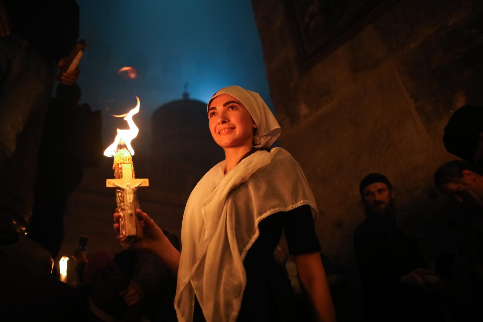 """Christian Orthodox worshippers hold up candles during the ceremony of the """"Holy Fire"""" as thousands gather in the Church of the Holy Sepulchre in Jerusalem's Old City, on April 15, 2017, during Orthodox Easter ceremonies. The ceremony celebrated in the same way for eleven centuries, is marked by the appearance of """"sacred fire"""" in the two cavities on either side of the Holy Sepulchre."""