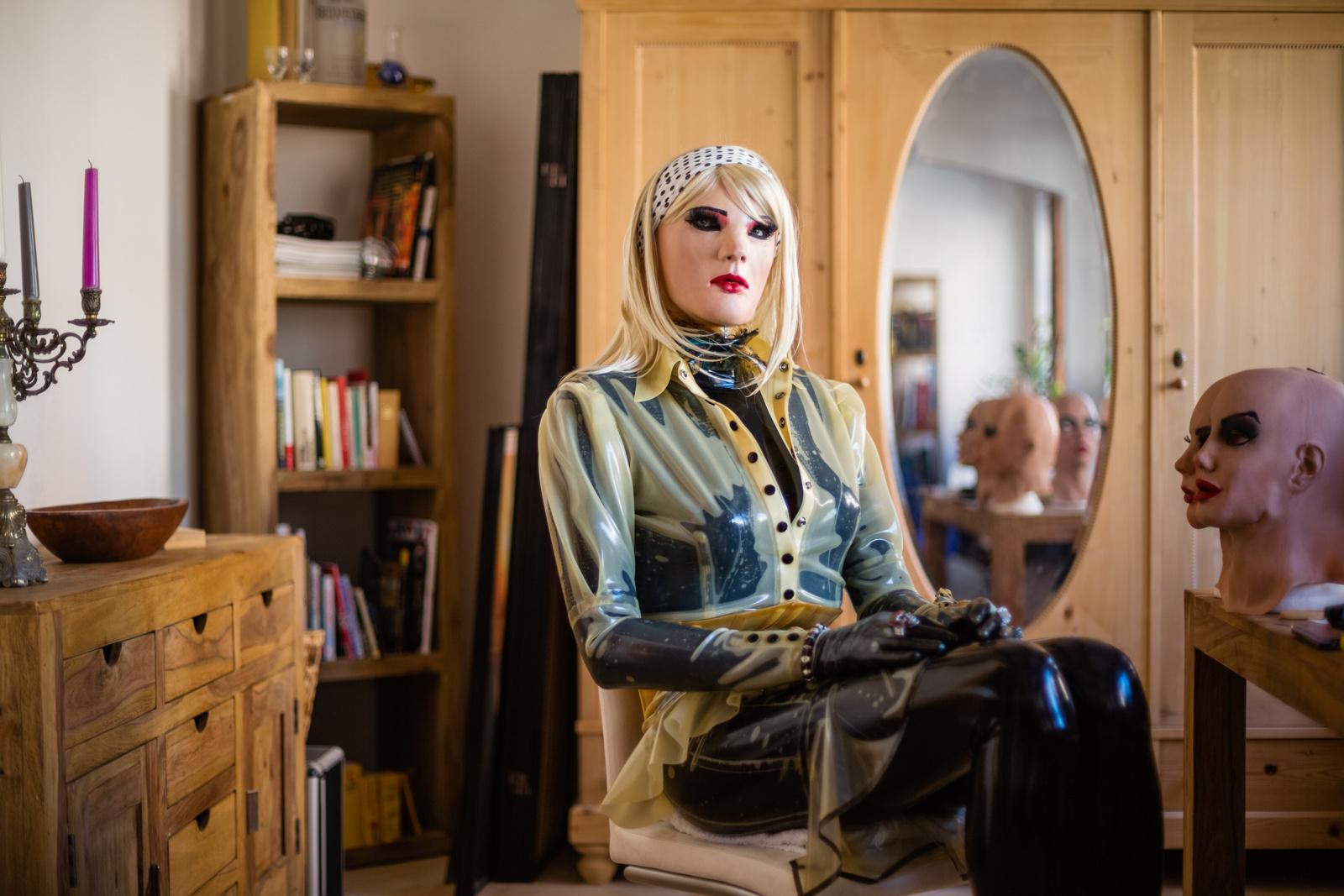 """AUGSBURG, GERMANY - AUGUST 05, 2015: Portrait of female masker Christian alias 'Chrissie Seams', double the age of his alter ego, in his living-room, August 05, 2015 in Augsburg, Germany. Female masking presents an outlet for him, as a heterosexual and cisgender male, to live out his female side and latex fetish. On his right stand a variety of masks that he uses for experimenting with airbrushing and other alteration techniques in order to individualise the look of his alter ego. """"Since my childhood I have been fascinated by latex, which very soon merged with my aspirations to look as sexy as a woman. I remember the first time I had the wish to slip into a woman's skin was at the age of 14 when I saw a model wearing sexy lingerie in a Penthouse magazine. I imagined slipping into her skin, like slipping into a surface made from latex. I love the feeling of being encapsulated and the sensitization from head to toe when wearing latex. At the same time I endeavor aesthetics. Visually, I only like latex on women, hence I don't gain anything from my fetish if not dressed as a woman myself. Many times I wondered if there was a Chrissie if it wasn't for my passion for latex."""" - Female masker Christian alias Chrissie Seams, heterosexual man, double the age of his alter ego"""