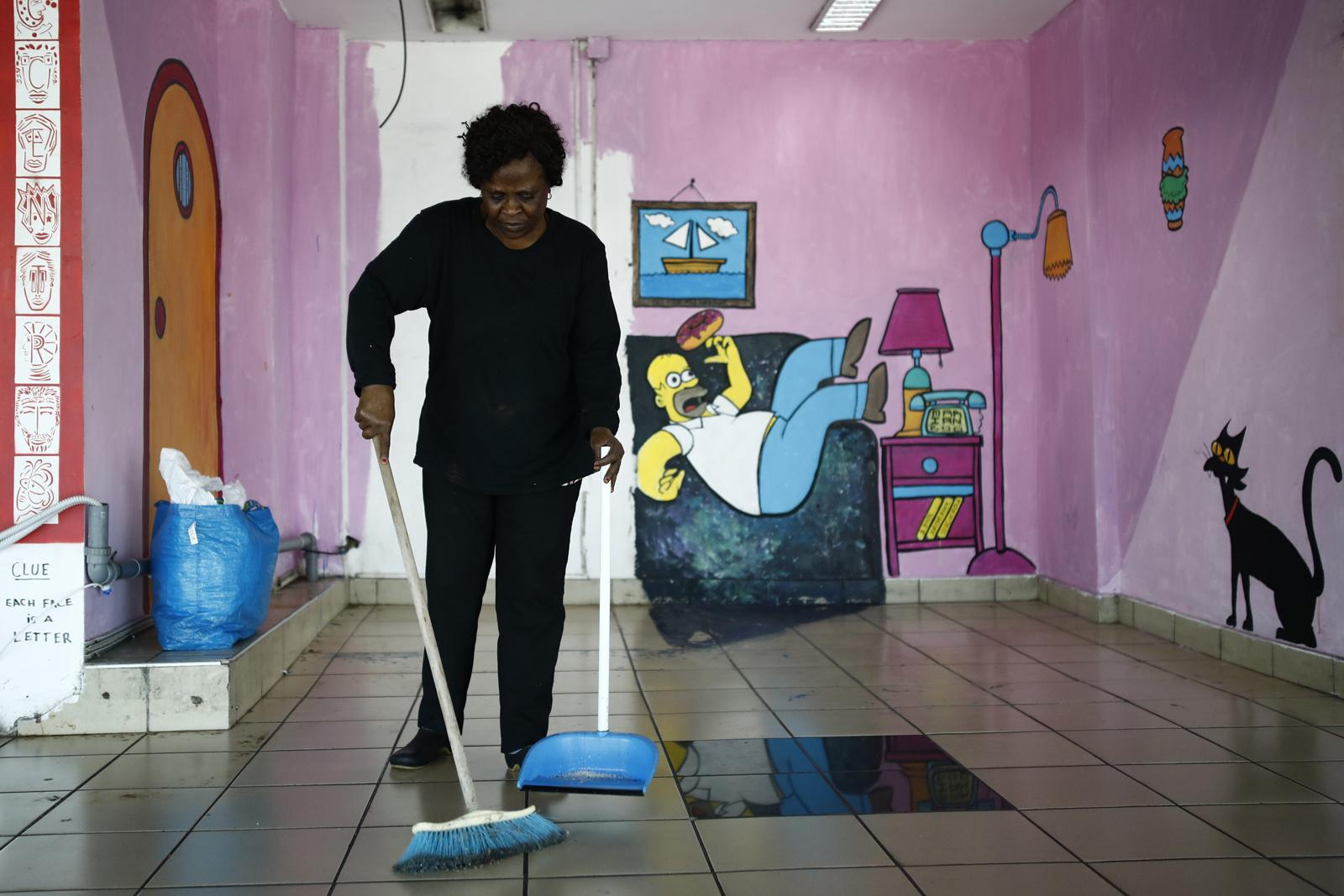 A woman cleans the floor in a space that functions as a gallery displaying street art, close to bus terminals on an upper floor of the Central Bus Station in Tel Aviv, Israel May 29, 2019.
