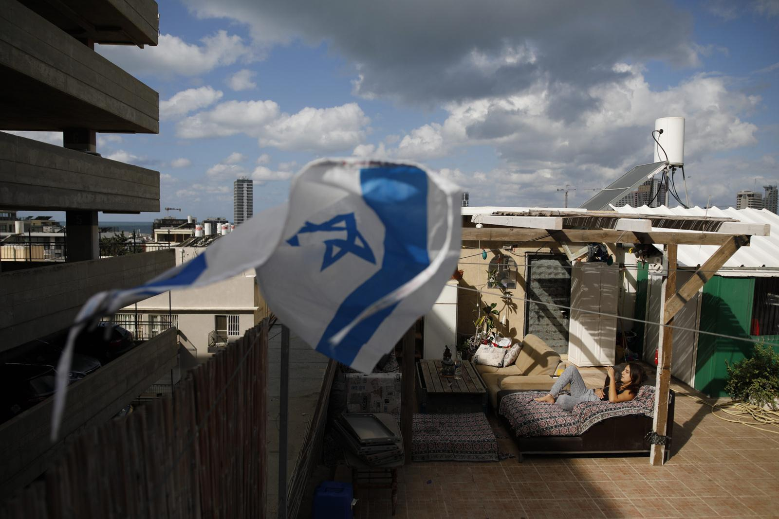 Maayan Saidi, 28, enjoys a cigarette on her rooftop, which is located right next to the Gruzenberg multi-storey car park (left), November 22, 2017, Tel Aviv, Israel. Her brother Idan plans to set up a hydroponic system on the rooftop.