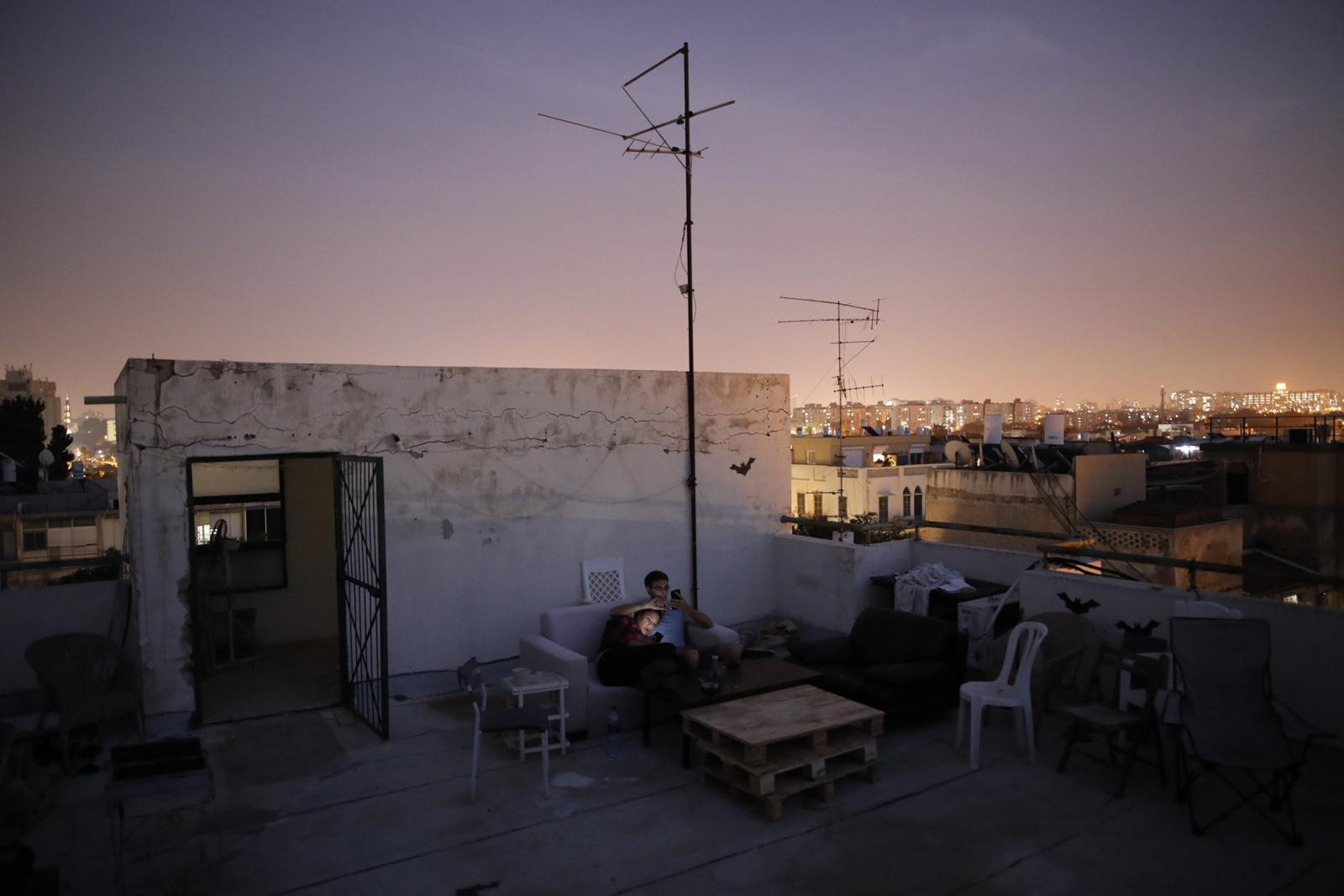 Hana Wimberly, 26, and Emanuel Cohen, 36, spend their evening together on a shared roof of a building in Yafo, Tel Aviv, November 18, 2017, Israel.