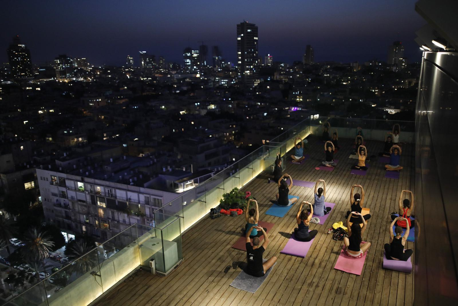 People participate in a yoga session on the rooftop of the city's municipality building, October 19, 2017, Tel Aviv, Israel.