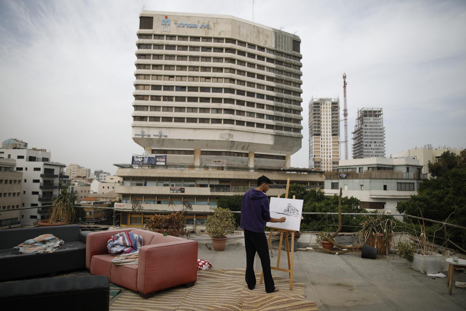 Hobby painter Kobi Malul, 31, paints on his rooftop in central Tel Aviv, November 13, 2017, Israel.