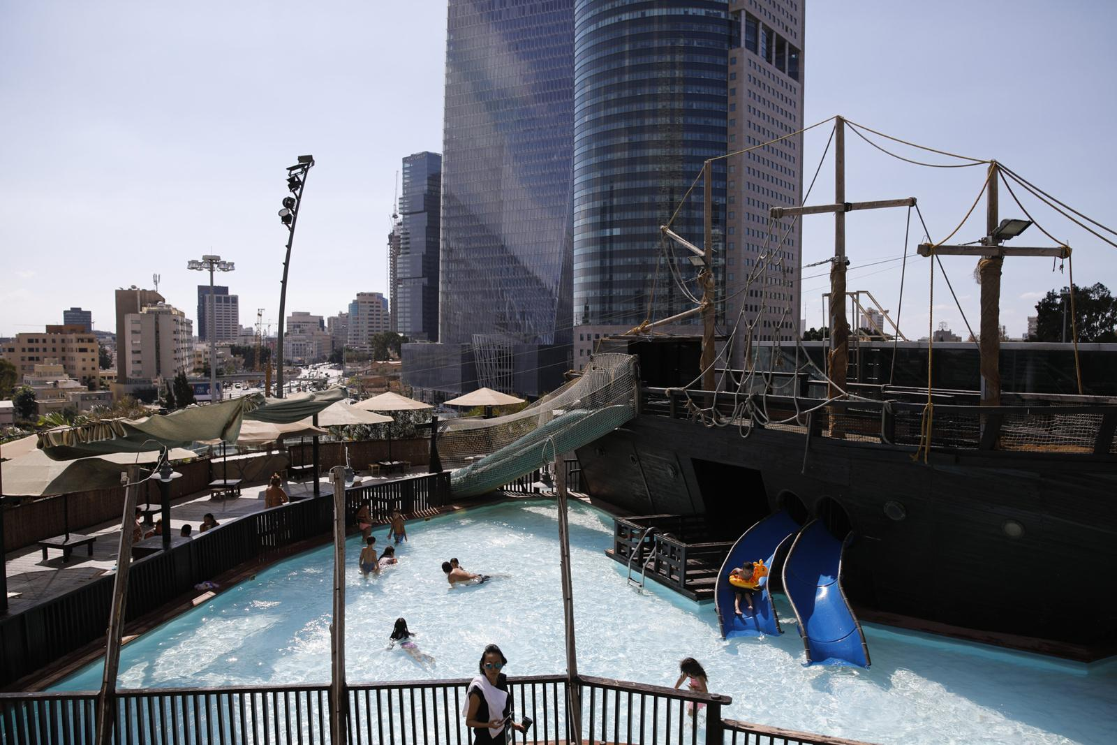 People bath in a swimming pool, which is part of a temporary entertainment park on the rooftop of Azrieli mall during the holidays of Sukkot, October 11, 2017, Tel Aviv, Israel.