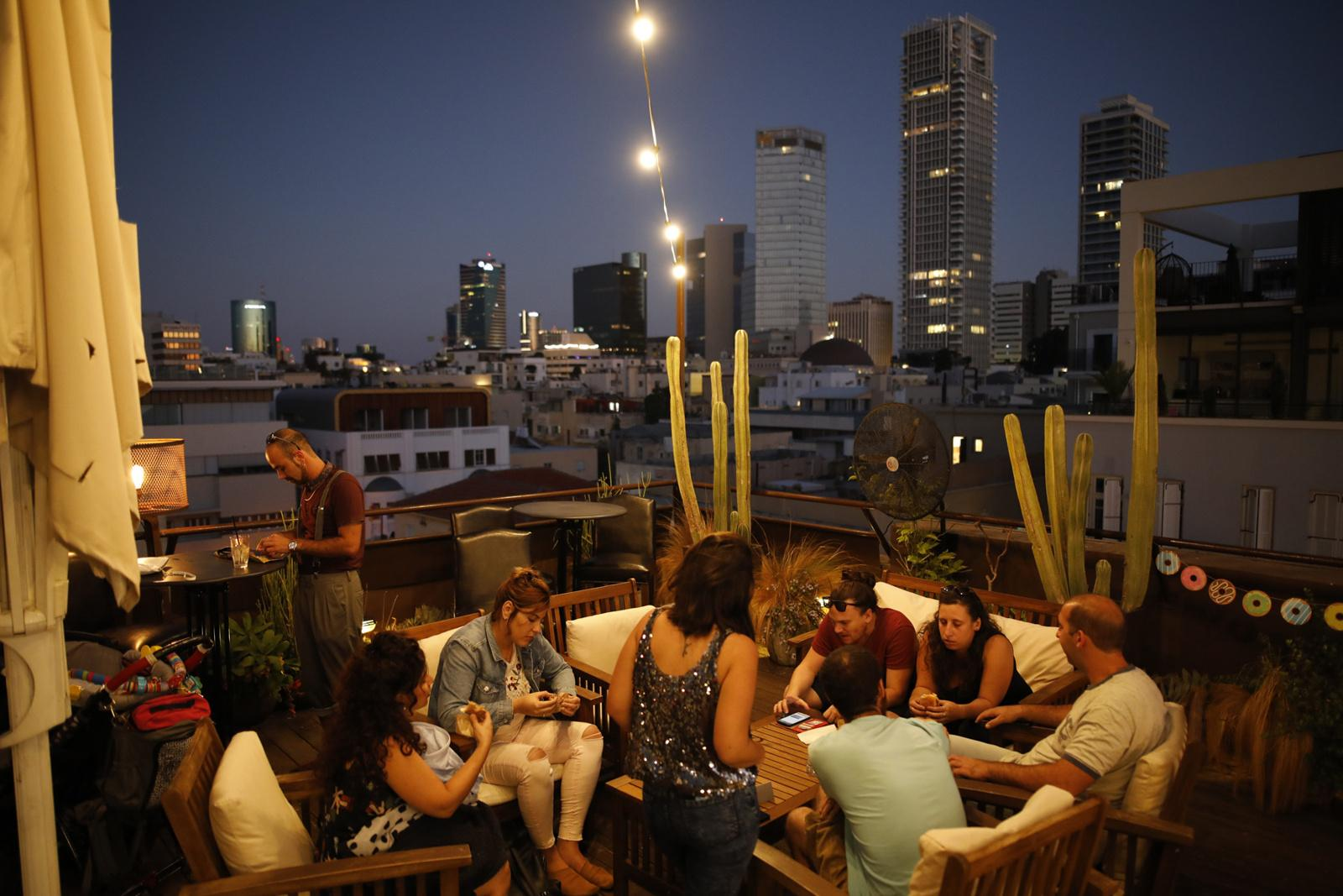 People socialize on the rooftop of the 'Brown Hotel', which serves as a public bar and space for events, October 14, 2017, Tel Aviv, Israel.