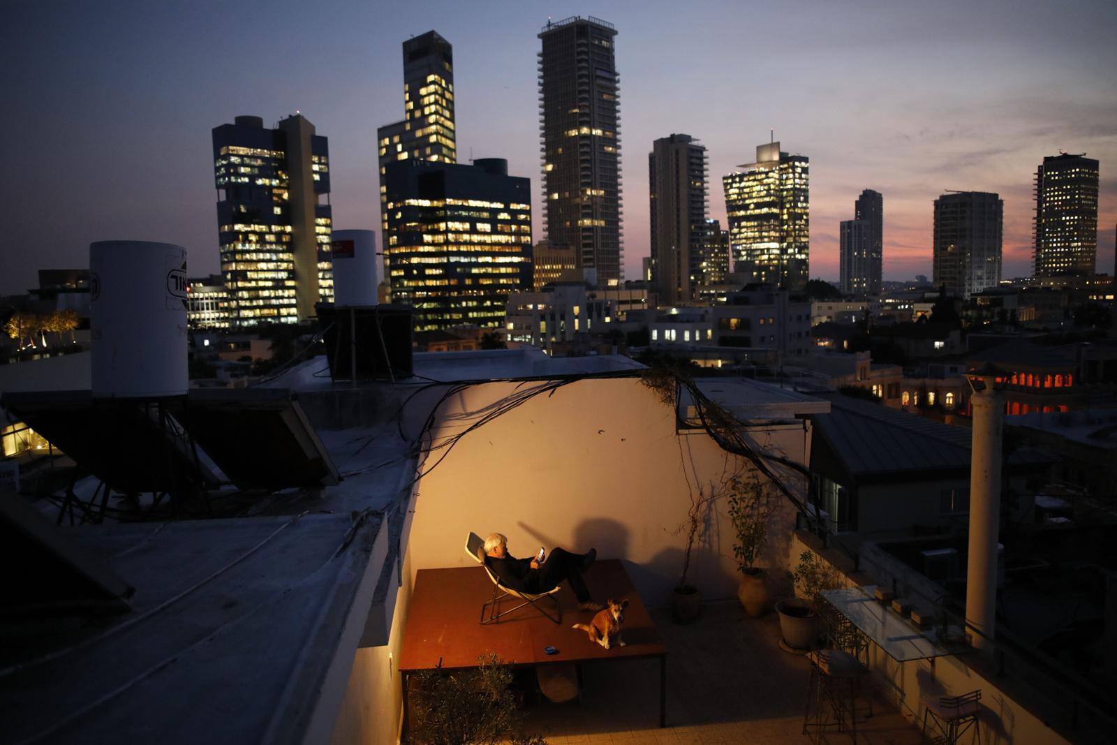 Alexander Flaschenberg, 60, sits on a chair ontop of a table, to enjoy the view on the sea from his rooftop, November 28, 2017, Tel Aviv, Israel. His rooftop presents a personal haven for him, giving him an opportunity to unwind from his work.