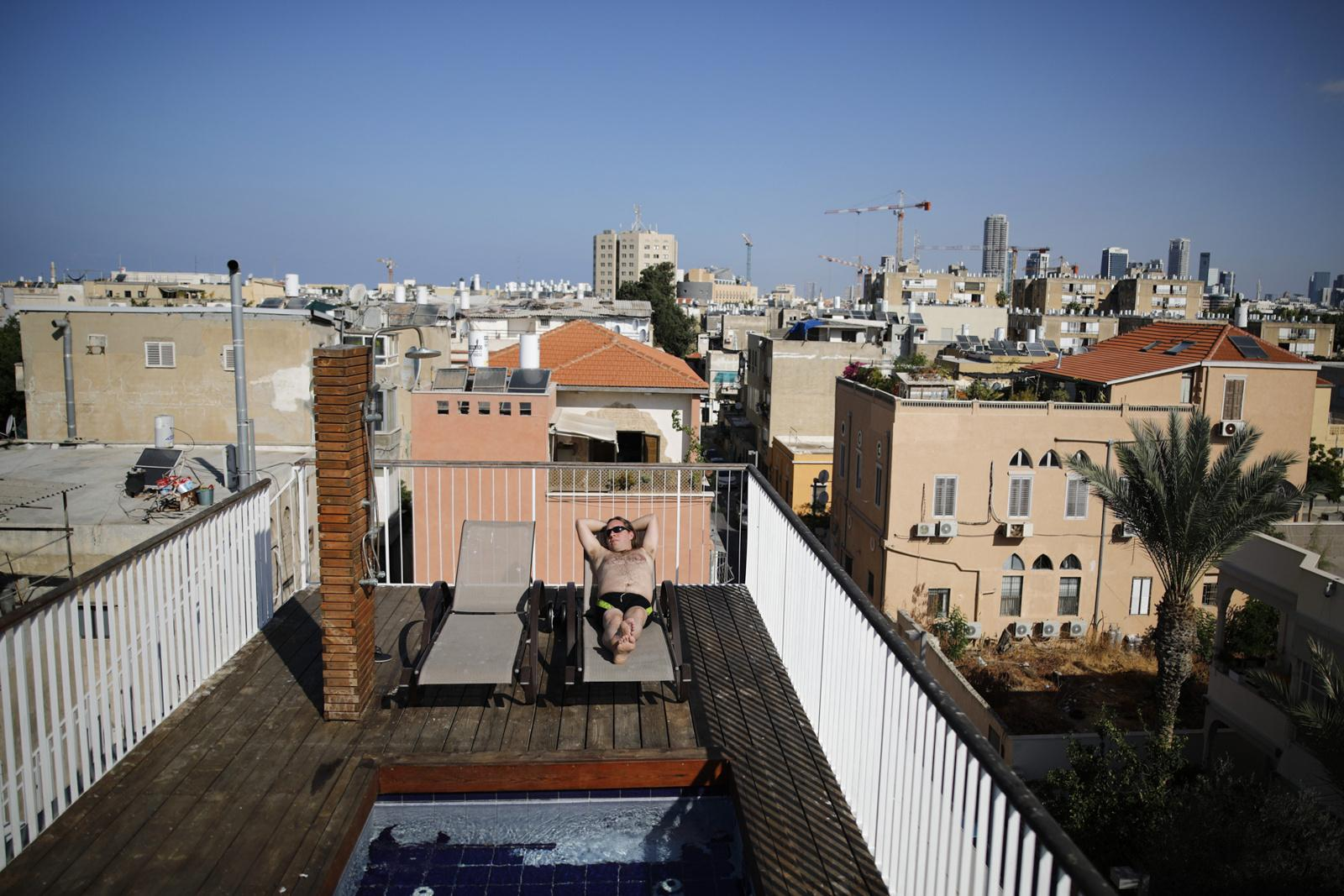 Aviah Morag, 35, relaxes on his rooftop in Yafo, equipped with a small pool, shower and sun loungers, November 10, 2017, Tel Aviv, Israel.