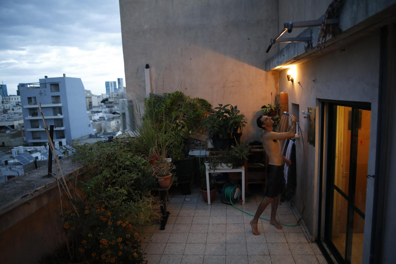 Emanuel Cohen, 36, takes a shower on his rooftop, which he also uses as a small garden to grow herbs and vegetables, November 24, 2017, in Florentine area, Tel Aviv, Israel. If the weather allows, Emanuel uses the outdoor shower instead of the indoor shower every day.