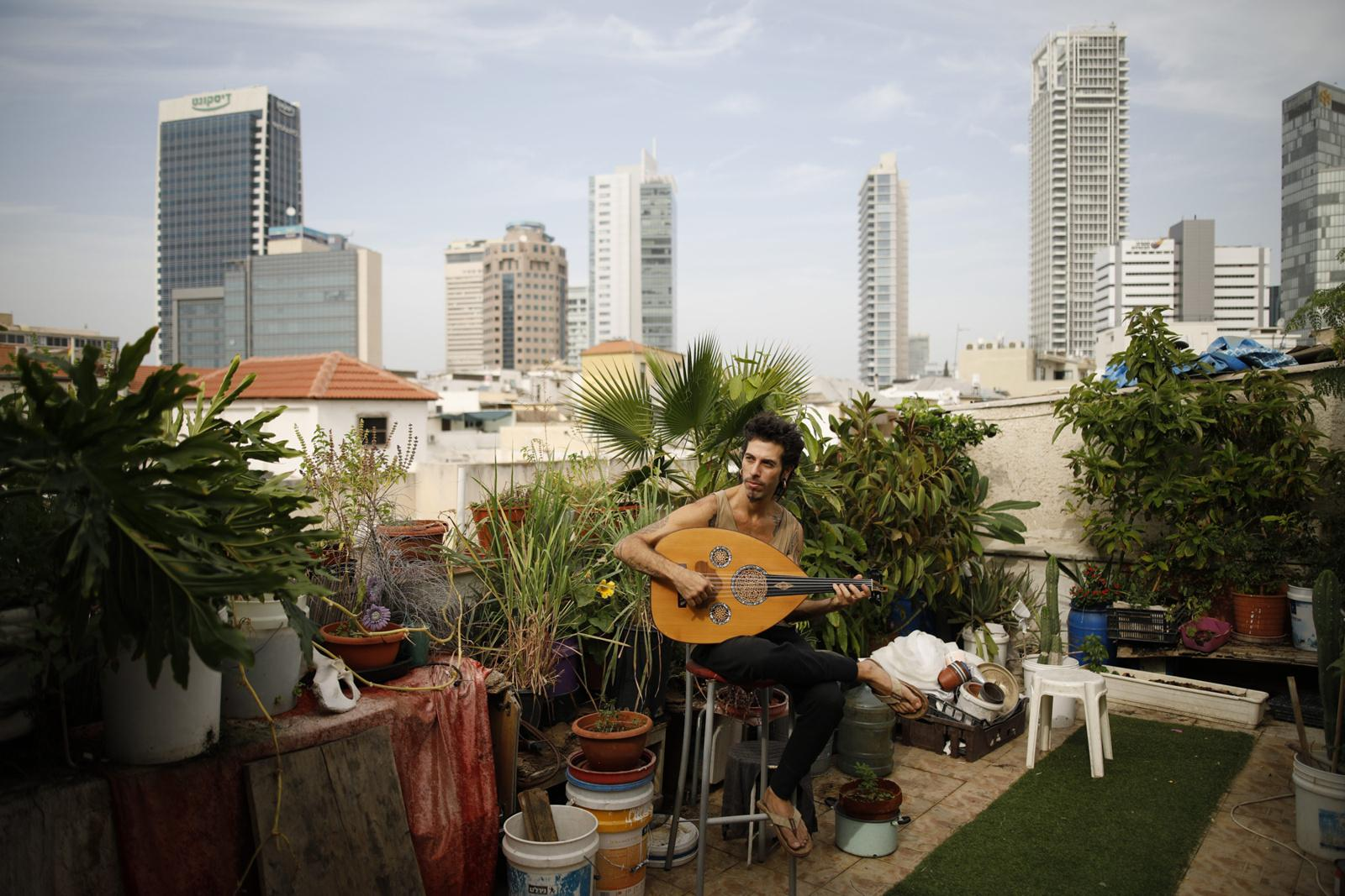 Musician Iyar Semel, 38, plays on his Oud in his rooftop garden, where he and his two other flatmates grow herbs and vegetables, November 13, 2017, Florentin, Tel Aviv, Israel.