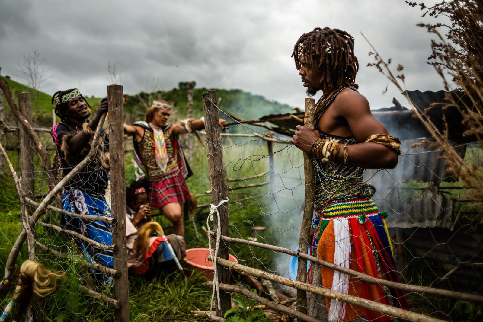 MDAKANE, LUSIKISIKI DISTRICT, SOUTH AFRICA - NOVEMBER 29, 2014: A group of sangomas stands in a dedicated area where they burn the bones of the sacrificed animals on November 29, 2014 in Mdakane, Lusikisiki District, South Africa. The burning of the bones officially marks the end of a traditional ceremony and is part of the 'old person's' symbolic death in whose place the animal died.