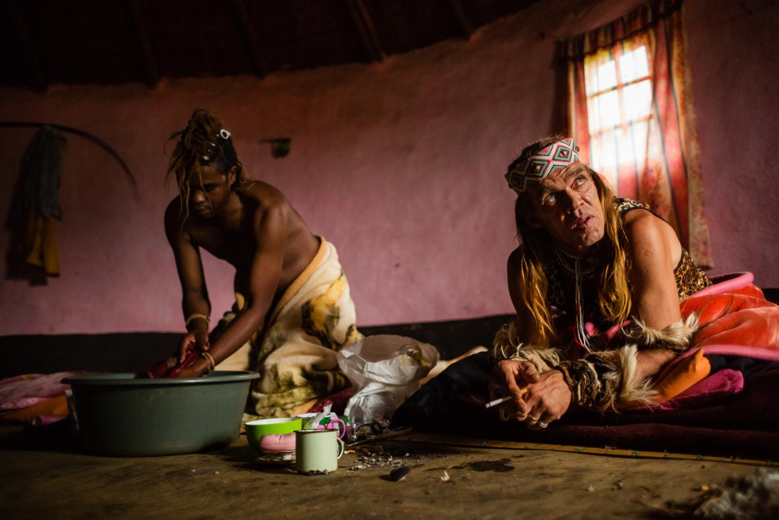 UMZIZWANGA, LUSIKISIKI DISTRICT, SOUTH AFRICA - NOVEMBER 13, 2014: Sangoma Chris Ntombemhlophe Reid (R ), 50, smokes a cigarette on his bed at his spiritual family's homestead while sangoma Ntombethongo (L), 37, washes himself on November 13, 2014 in Umzizwanga, Lusikisiki District, South Africa. It is the first morning of a month long stay in the rural areas of the transkei during that various traditional ceremonies will be performed. The round hut, used as a communal sleeping space, will then transform into the ceremonial area.
