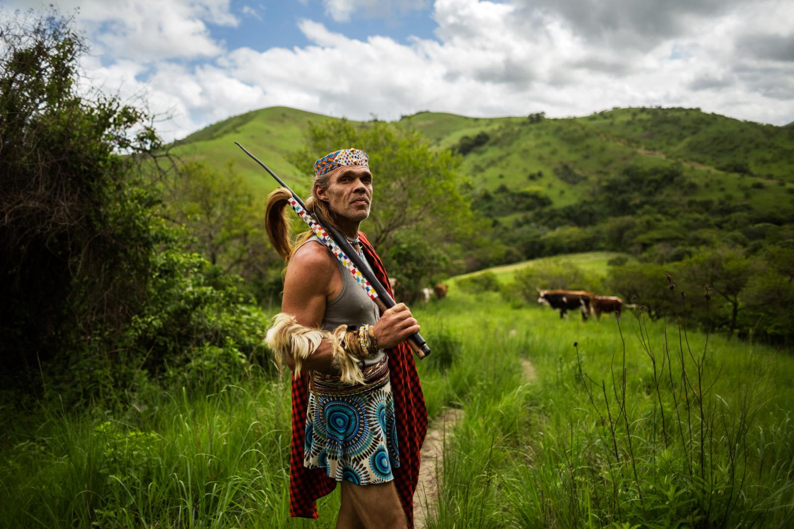 MDAKANE, LUSIKISIKI DISTRICT, SOUTH AFRICA - NOVEMBER 17, 2014: Holding his wip and itshoba (cow-tail whisk) in his hand, Chris Ntombemhlophe Reid, 50, pauses his walk through the rural areas of the transkei to check on his thwasa (sangoma trainee) Nolwandle on November 17, 2014 in Mdakane, Lusikisiki District, South Africa. Since thwasas are not allowed to walk among cows before they dream 'their cow' as an offering to their ancestors and the last step of their training, Chris Ntombemhlophe Reid wants to make sure that Nolwandle walks around the cows. The wip and itshoba are traditional sticks that indicate the status of a sangoma and serve as means to connect to the ancestors. During journeys sangomas carry at least one in their hands as a sign of respect.