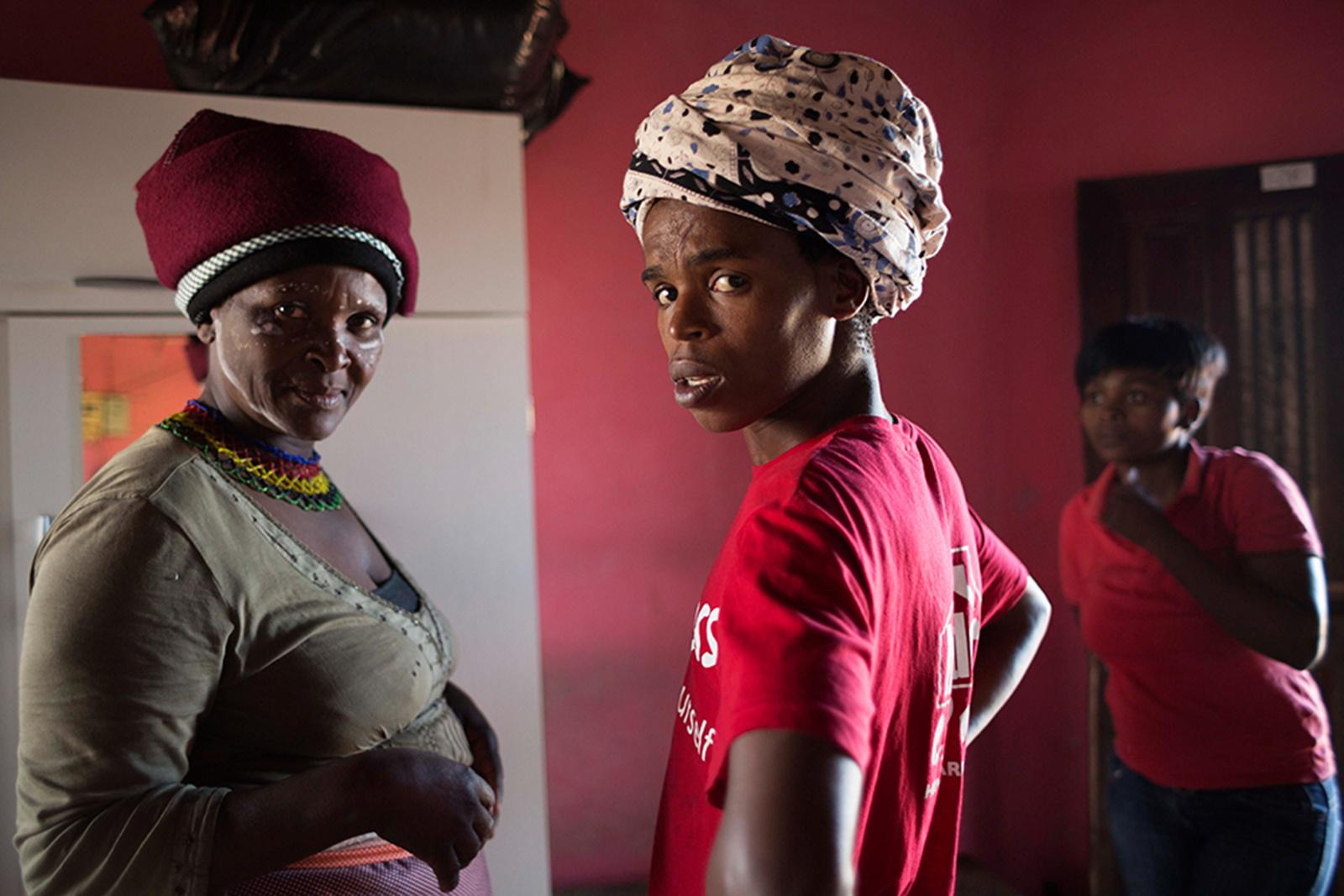NGXINGXOLO, MOOIPLAAS, EAST LONDON, SOUTH AFRICA - OCTOBER 03, 2014: Transgender woman Lazola Canzibe (C), 24, visits her cousin Nolusapho Ndoyana (L), currently wearing traditional clothing, and her niece Nontombi Ndoyana (R) October 03, 2014 in Ngxingxolo, Mooiplaas, East London, South Africa. Living quite far away in Kwelera, Lazola has the chance to visit them today because she helps with preparations for a traditional ceremony taking place close to her cousin's home within the upcoming days. The ceremony is devoted to a praisal of ancestors on October 04 followed by a celebration on October 05. Rural areas, such as Ngxingxolo, are strongly shaped by traditional practices and gender roles. Identifying as a female, Lazola sticks to the traditional gender role of women whose main duties are cleaning, cooking, fetching water, collecting firewood and looking after the children.