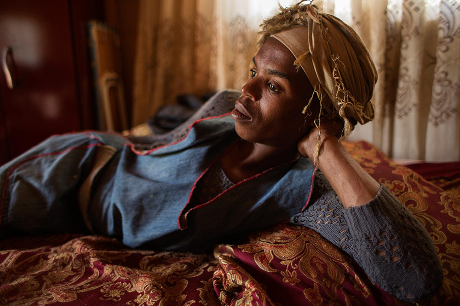 KWELERA, EAST LONDON, SOUTH AFRICA - AUGUST 27, 2014: Transgender woman Lozola Lanzibe, 24, lies on her bed wearing traditional Xhosa clothing August 27, 2014 in Kwelera, East London, South Africa. Identifying as a female, Lazola sticks to the traditional gender roles in her community in that women are the homekeepers whose main duties are cleaning, cooking, fetching water, collecting firewood and looking after the children.