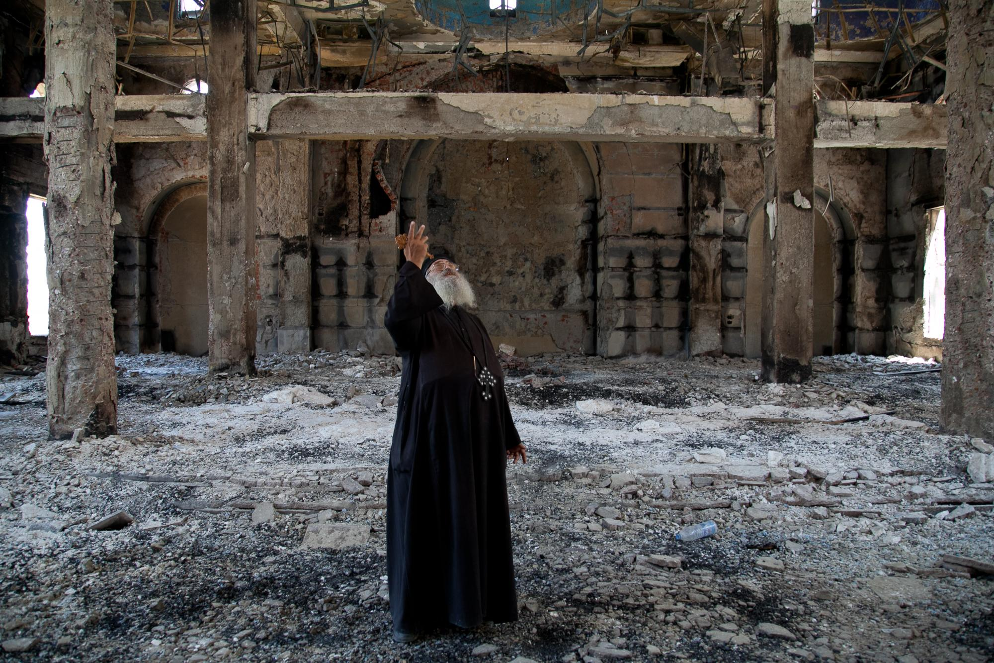 Al-Anba Mousa church in Minya was attacked by groups of men on August 14, 2013, who were pro-Mohamed Morsi supporters. Father Samuel Aziz Abdou looks up holding his cross in disbelief.