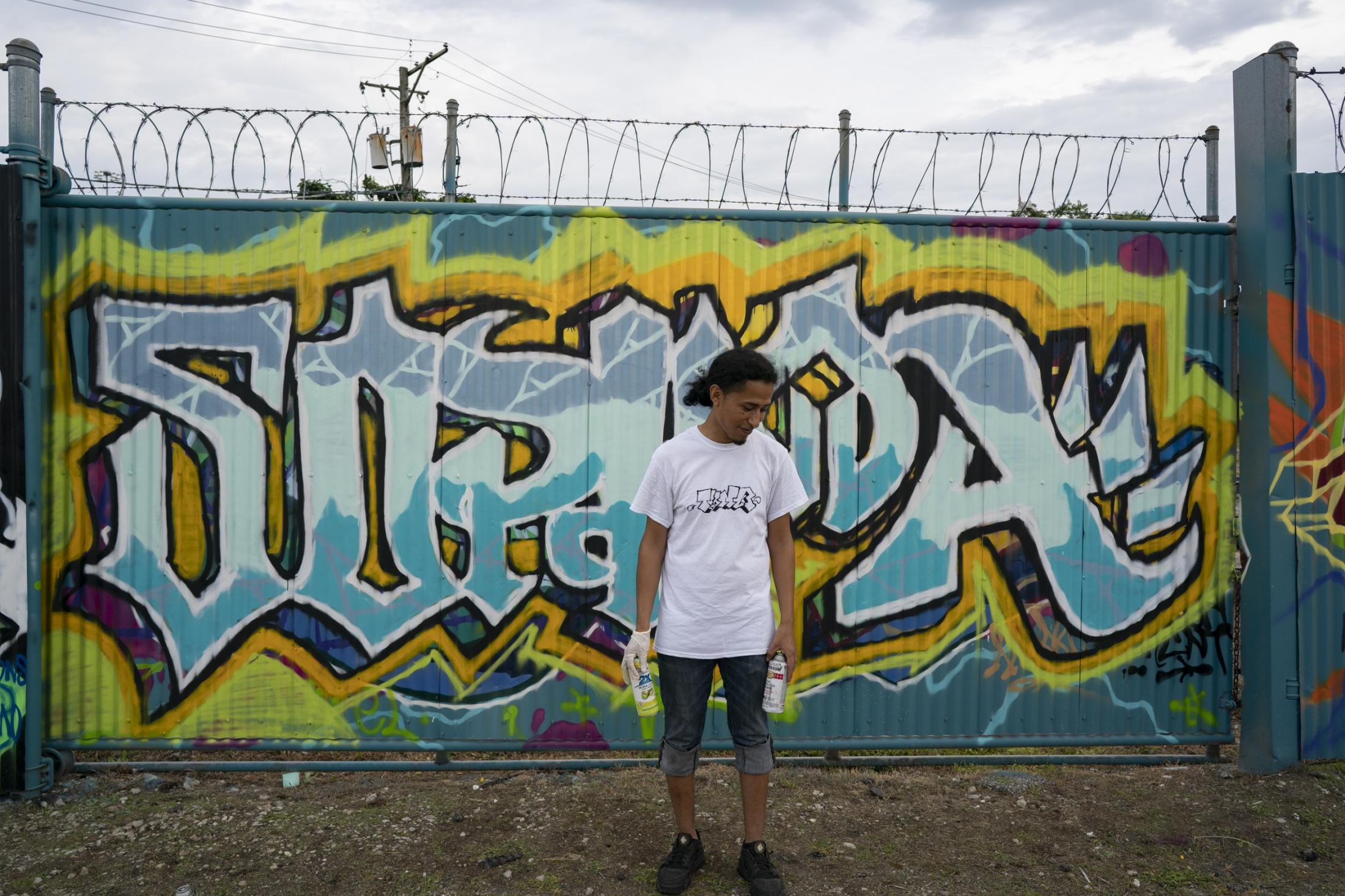 "Pedro Meza stands next to a piece he painted across the street from the Cook County Jail during the Meeting of Style graffiti art event in Chicago. Meza said he lost custody of his now 6-year-old daughter, Sophia, after his divorce six years ago. Over the past three years, Meza has painted her name around his neighborhood to honor her. ""This is what I can do for her,"" he said. ""Maybe someday she'll know."""
