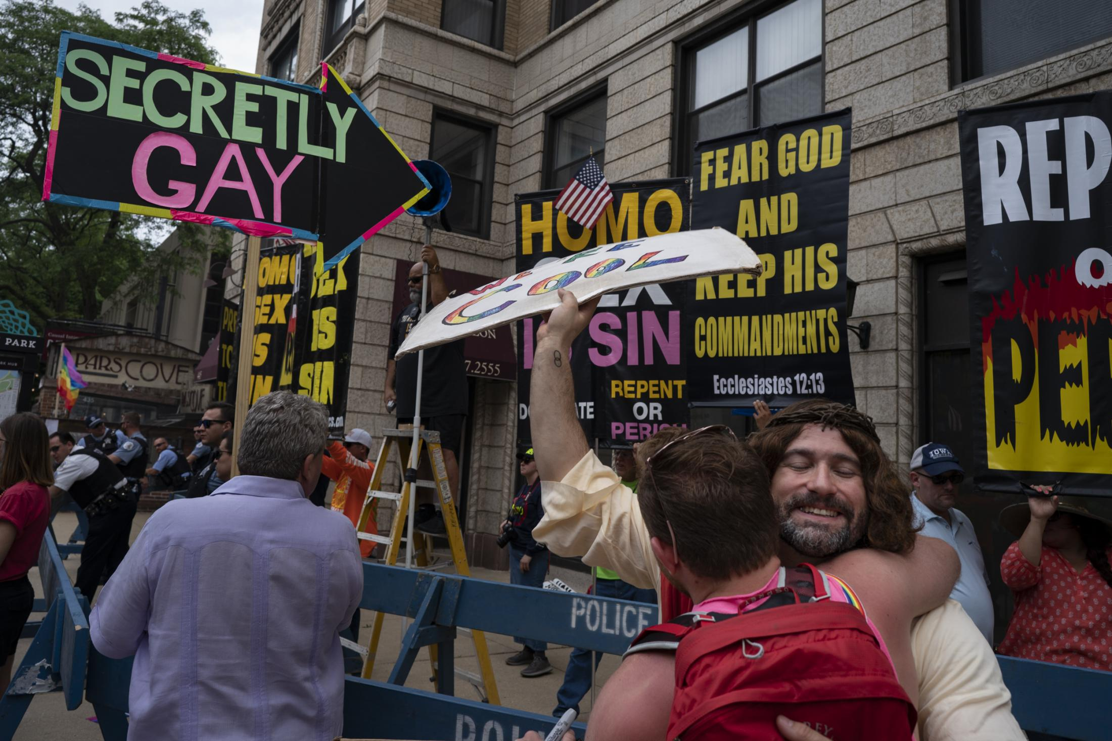 "Scott Whitehair, dressed as Jesus Christ, gives out free hugs to counter-protest a Christian hate group during Chicago's 50th Pride Parade on June 30, 2019. ""I showed up because it's a chance to make people laugh and smile when they walk by instead of hearing this terrible stuff,"" Whitehair said."