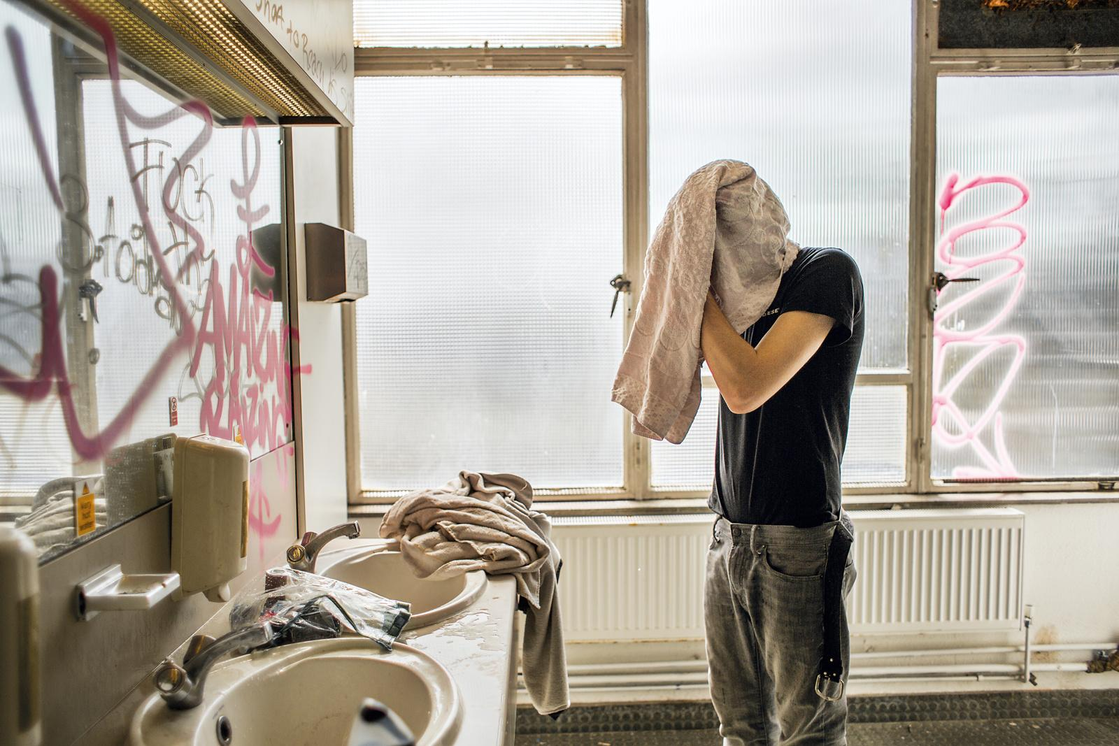 LONDON, UNITED KINGDOM - MAY 09, 2013: A resident washes his hair in the communal washrooms in a squat called 'The Castle' on May 09, 2013 in London, United Kingdom. Once used as a five-storey office block, the building then accommodated more than 100 squatters and was used as a location for parties. Squatting is often a conscious choice of an alternative and communal way of living. On 1st of September 2012 the new section 144 of the Legal Aid Sentencing and Punishment of Offenders Bill (LASPO) came into force rendering squatting in residential buildings a criminal offence. Hence, squatting can legally only be attempted in commercial premises with the result that squatters often occupy unusual premises that contradict the conventional idea of home.