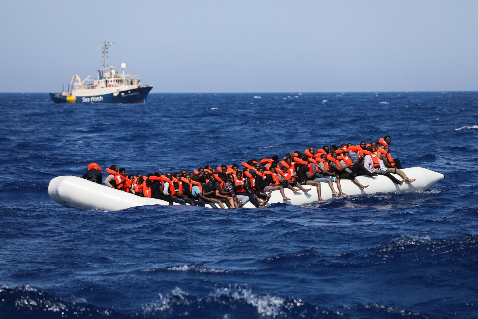 Refugees sit on a dinghy wearing life jackets that they were given by NGO workers, while the rescue vessel 'Sea Watch' is seen in the background, on the Mediterranean sea off the Libyan coast, June 03, 2017. Two rescue vessels were involved in the rescue mission, 'Sea Watch' and 'Vos Hestia', which took the refugees on board. The sea journey took the lives of four migrants. The Central Mediterranean route is the world's deadliest migration route. Of the estimated 3,080 people that have died or gone missing while trying to reach Europe by sea via the three Mediterranean routes until end of November 2017, over 94% of deaths have occurred from North Africa to Italy, according to UNHCR. Over 117,000 refugees and migrants arrived in Italy by sea in 2017, about 32% less compared to 2016.
