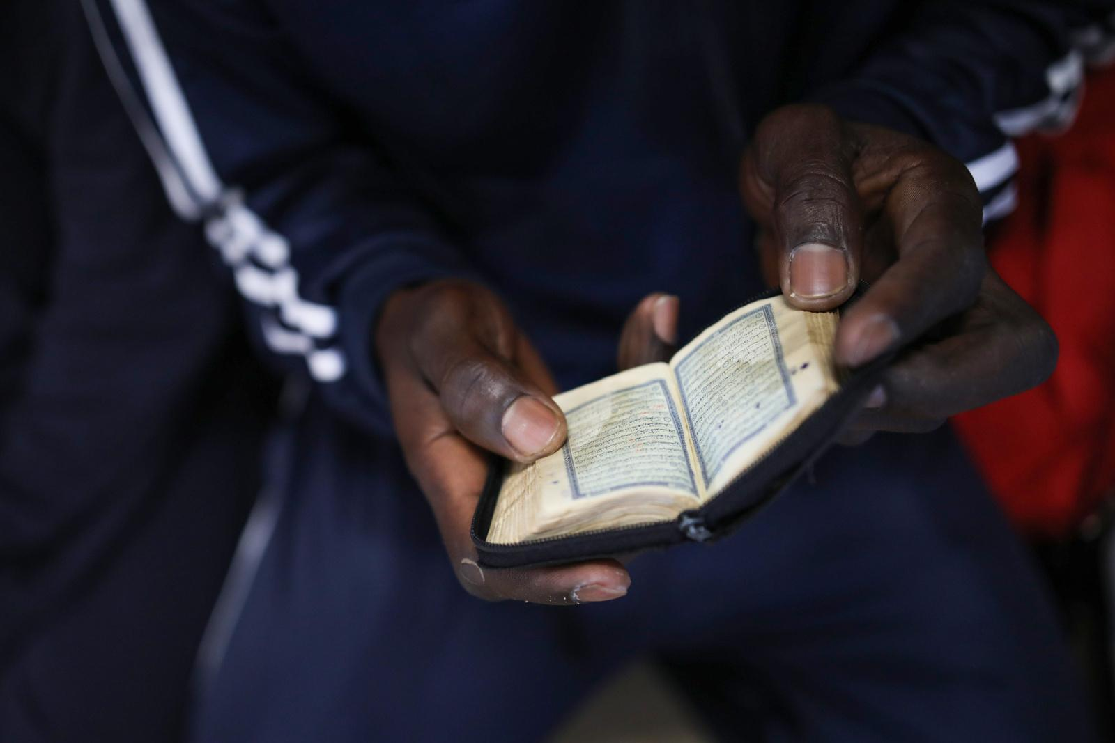 A refugee prays while reading from a small Quran, on deck of the rescue vessel 'VOS Hestia', a few hours after having been rescued from a dinghy on the Mediterranean sea off the Libyan coast, June 03, 2017. The sea journey took the lives of four migrants. The Central Mediterranean route is the world's deadliest migration route. Of the estimated 3,080 people that have died or gone missing while trying to reach Europe by sea via the three Mediterranean routes until end of November 2017, over 94% of deaths have occurred from North Africa to Italy, according to UNHCR. Over 117,000 refugees and migrants arrived in Italy by sea in 2017, about 32% less compared to 2016.