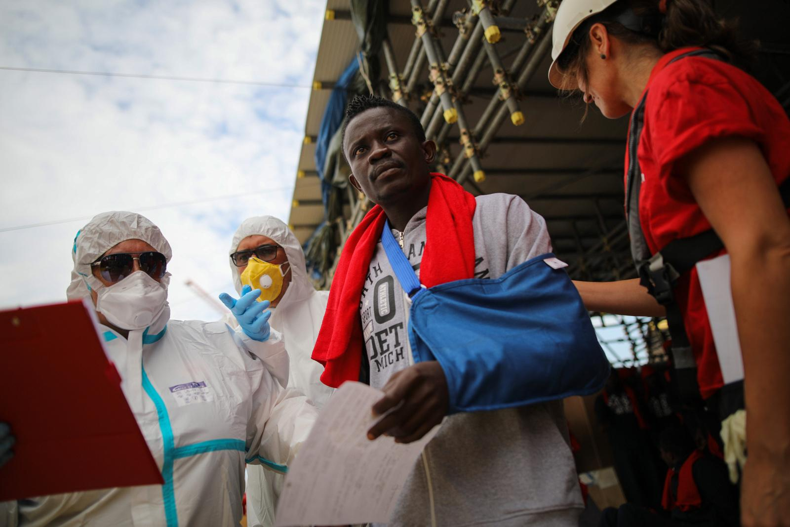 A medical contagion prevention team (left) and a doctor (right) bring a refugee from board of the rescue vessel 'VOS Hestia', in the port of Trapani, Italy, June 05, 2017. The Central Mediterranean route is the world's deadliest migration route. Of the estimated 3,080 people that have died or gone missing while trying to reach Europe by sea via the three Mediterranean routes until end of November 2017, over 94% of deaths have occurred from North Africa to Italy, according to UNHCR. Over 117,000 refugees and migrants arrived in Italy by sea in 2017, about 32% less compared to 2016.