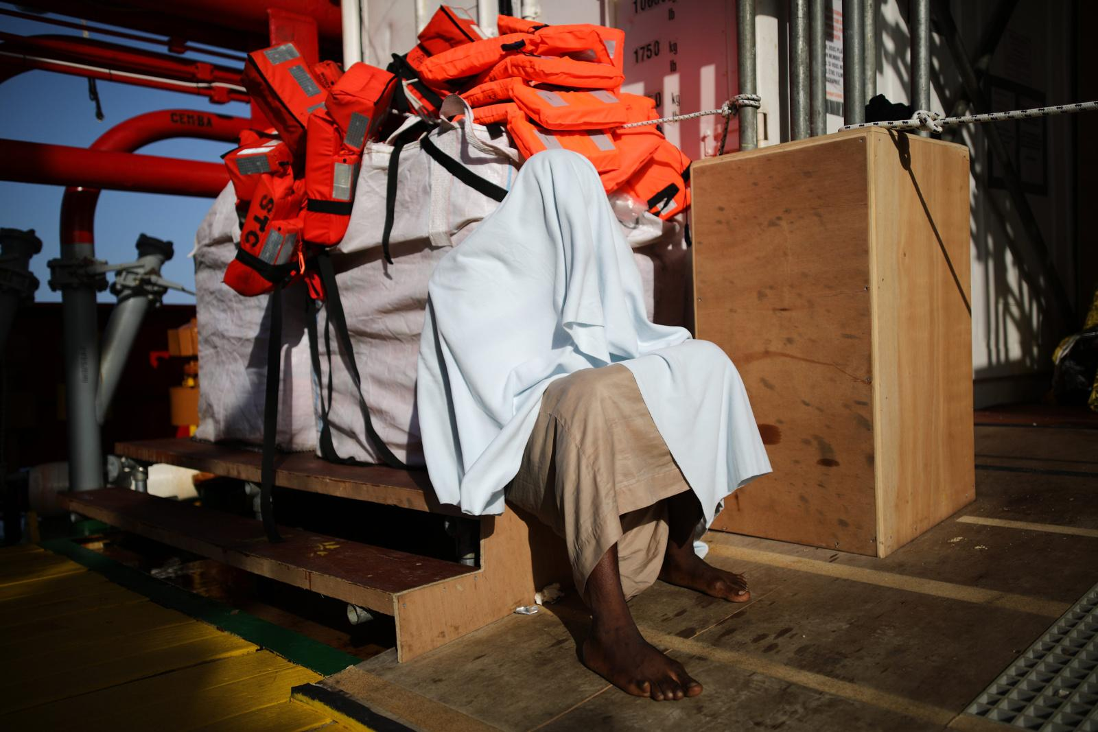 A refugee wrapped in a blanket grieves in front of the morgue on the rescue vessel 'VOS Hestia', after having been rescued from a dinghy on the Mediterranean route from Libya to Italy, June 03, 2017. The sea journey took the lives of four migrants. The Central Mediterranean route is the world's deadliest migration route. Of the estimated 3,080 people that have died or gone missing while trying to reach Europe by sea via the three Mediterranean routes until end of November 2017, over 94% of deaths have occurred from North Africa to Italy, according to UNHCR. Over 117,000 refugees and migrants arrived in Italy by sea in 2017, about 32% less compared to 2016.