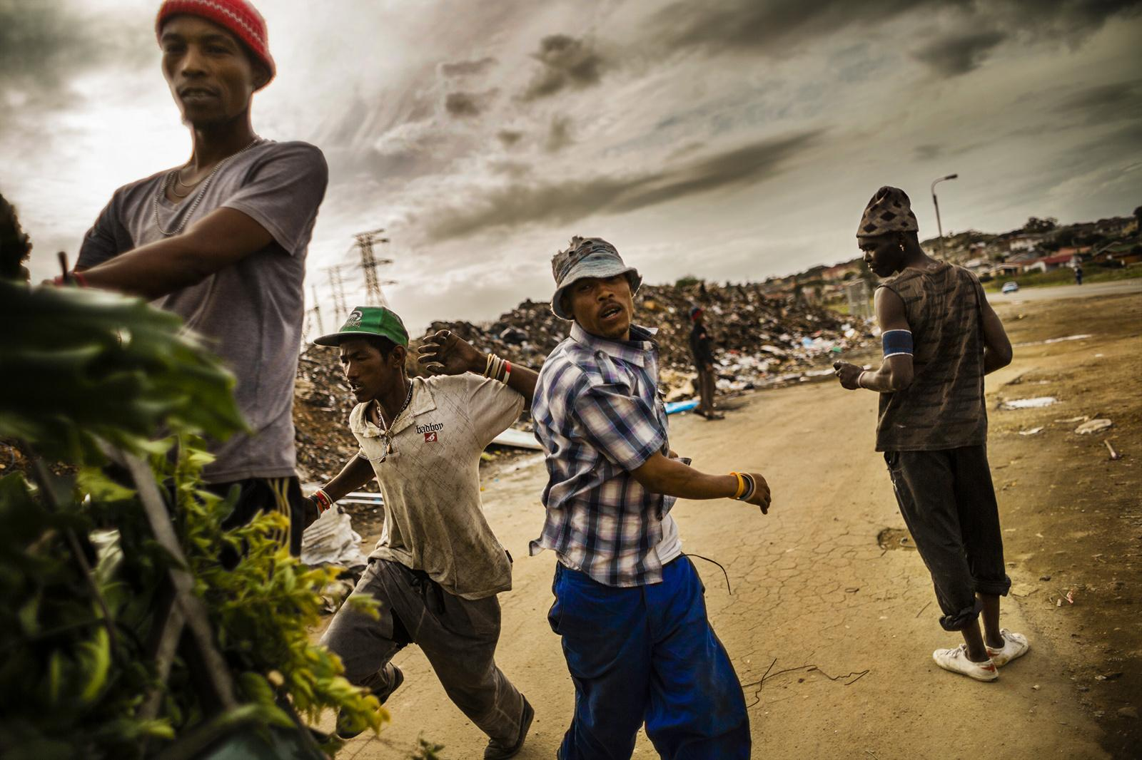 PORT ELIZABETH, SOUTH AFRICA - MARCH 06, 2015: Residents of a small community located next to a dumpsite run after a car to jump on its back March 06, 2014 in Port Elizabeth, South Africa. They make tips by helping people unload their garbage. Most of the people that stay here used to be associated with gangs and are now escaping this dangerous lifestyle. Many of them come from Helenvale, an area that is now home to approximately 21 gangs, hence nicknamed 'Katanga', after the war-stricken province of the Democratic Republic of Congo.
