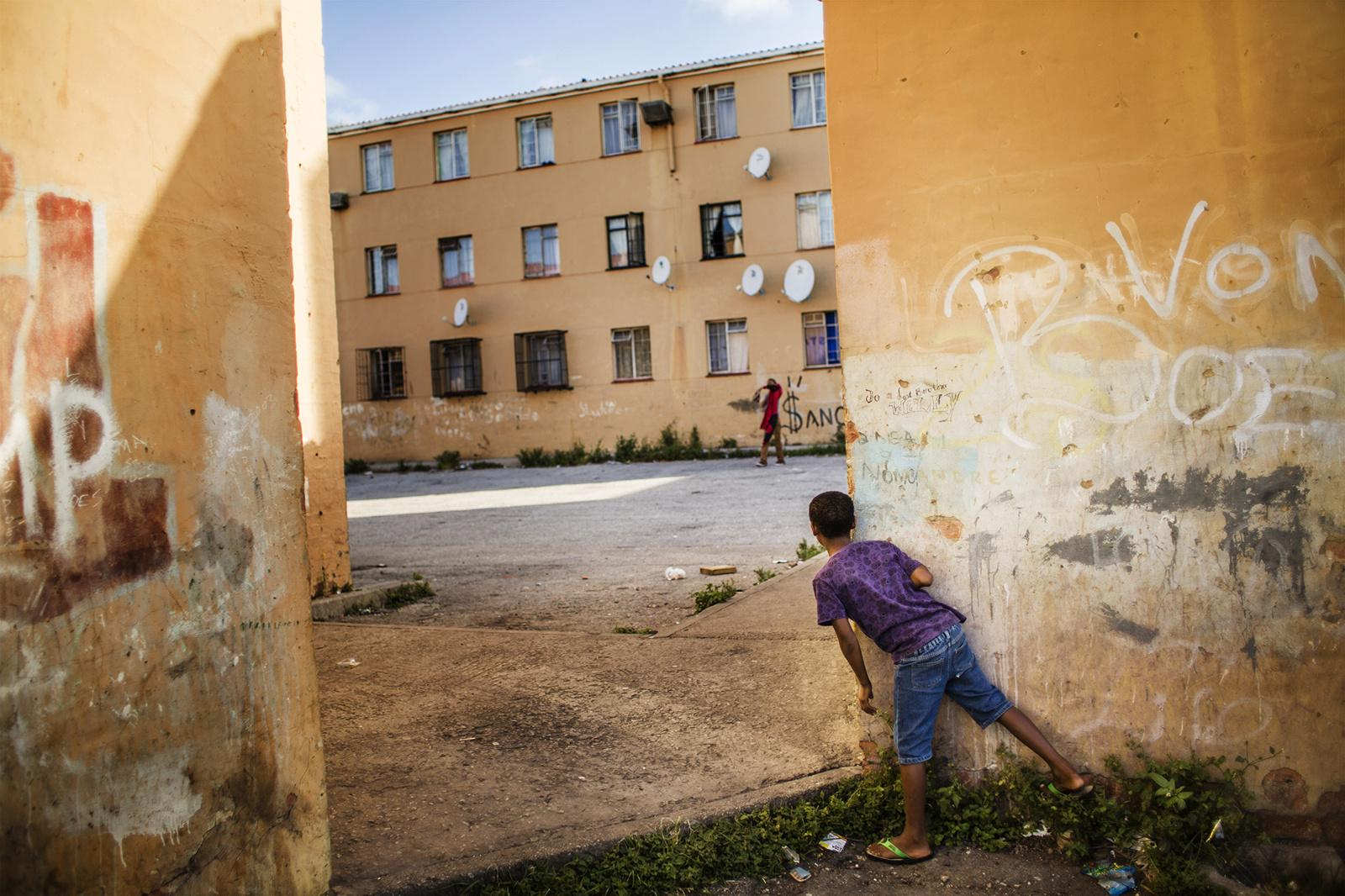 SCHAUDERVILLE, PORT ELIZABETH, SOUTH AFRICA - FEBRUARY 27, 2015: Children play at a flat complex in Schauderville, Port Elizabeth, South Africa on February 27, 2015. Schauderville is part of the Northern areas of Port Elizabeth where gangsterism is particularly high and sought after as an alternative means of survival and sense of belonging within the most marginalised of South Africa's ethnic groups, the coloured communities.