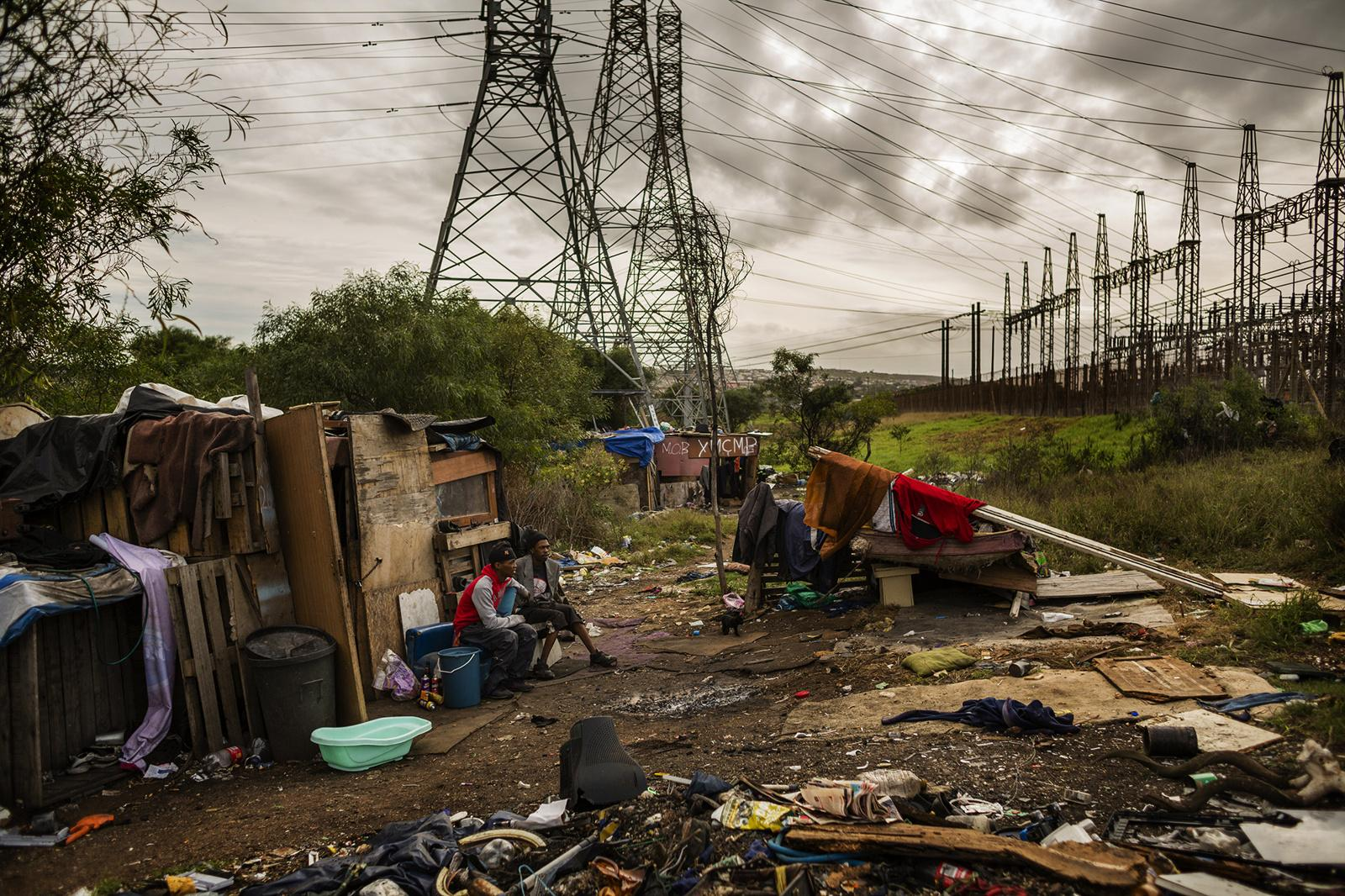 PORT ELIZABETH, SOUTH AFRICA - APRIL 06, 2015: Residents of a small community next to a dumpsite hang out in front of their shacks after a day of work April 06, 2014 in Port Elizabeth, South Africa. They make their living by tips for helping unload garbage off people's cars and reuse items. Most of the people that live at the dumpsite used to be associated with gangs and are now escaping this dangerous lifestyle. Many of them come from Helenvale, an area that is now home to approximately 21 gangs, hence nicknamed 'Katanga', after the war-stricken province of the Democratic Republic of Congo.