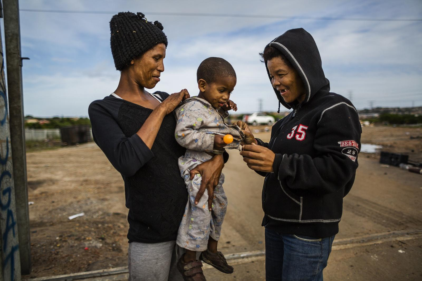 PORT ELIZABETH, SOUTH AFRICA - APRIL 06, 2015: A resident of a small community living next to a dumpsite holds her child in her arms while another resident sorts out items found in the garbage April 06, 2014 in Port Elizabeth, South Africa. The community makes their living by getting tipped helping unload people's cars and re-using or repairing items found on the dumpsite. Most of the people that stay at the dumpsite used to be associated with gangs and are now escaping this dangerous lifestyle. Many of them come from Helenvale, an area that is now home to approximately 21 gangs, hence nicknamed 'Katanga', after the war-stricken province of the Democratic Republic of Congo.