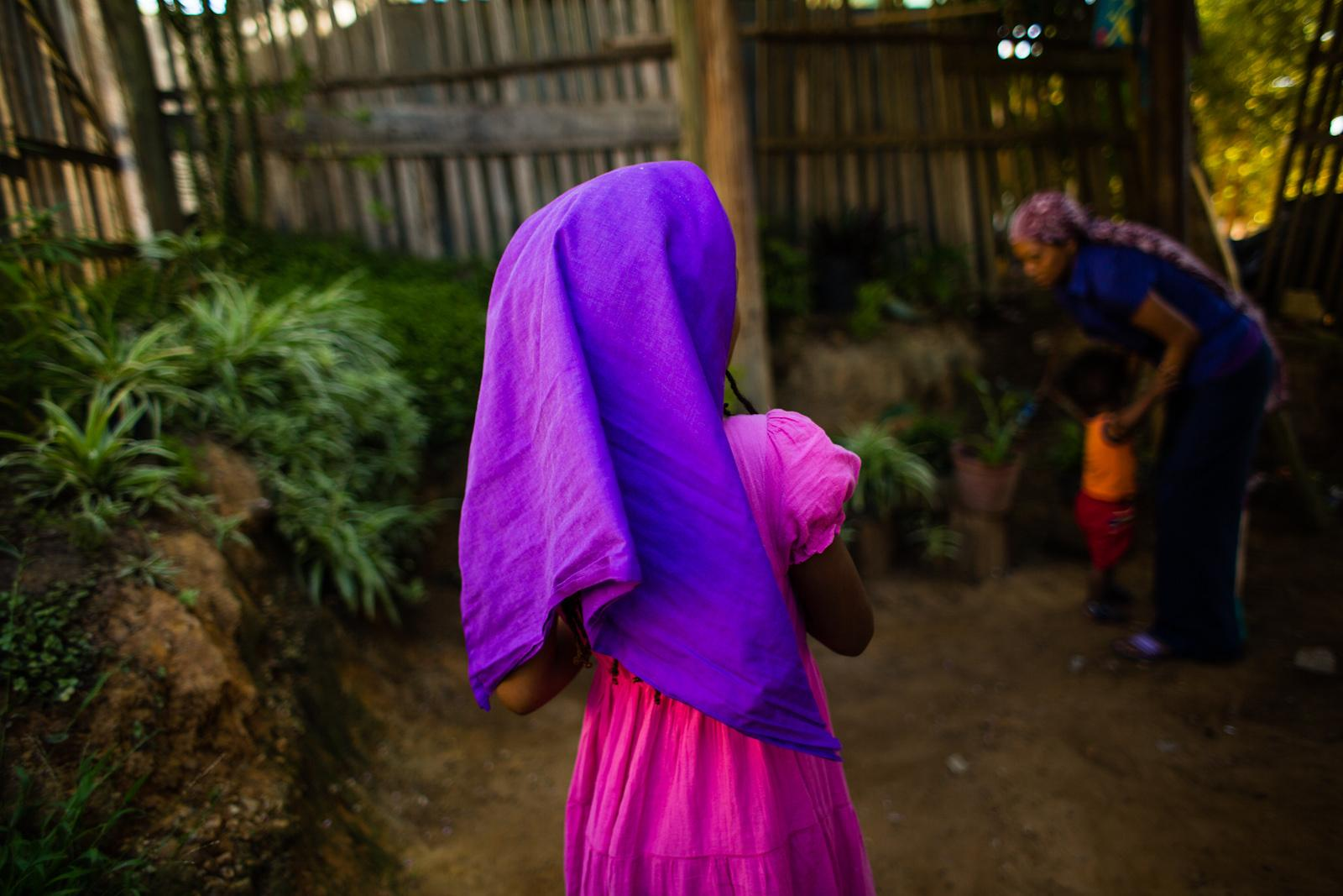 KNYSNA, SOUTH AFRICA - APRIL 12, 2015: Naphiteta (C ) stands in front of her home while her mother takes care of the youngest of her nine children in Judah Square, a Rastafari community in Knysna, South Africa on April 13, 2015. The family belongs to the 'Bobo Shanti', the strictes of the three mansions within Rastafari culture, which demands, among others, a constant covering of their hair.