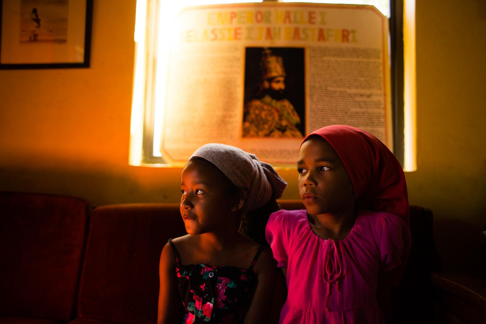KNYSNA, SOUTH AFRICA - February 08, 2015: During their Sunday's workshop, Empress (L ) and Naphiteta (R ) sit on a couch in front of a poster of Haile Selassie in the home of Sister Kerri at Judah Square, Knysna, South Africa on February 08, 2015. The workshops are designed to teach the children about Rastafari culture of that religion is an important part. The Rastafari movement is seen as an extension of Christianity, that praises Haile Selassie, Emperor of Ethiopia from 1930-1970, as the second coming of Jesus Christ on Earth.