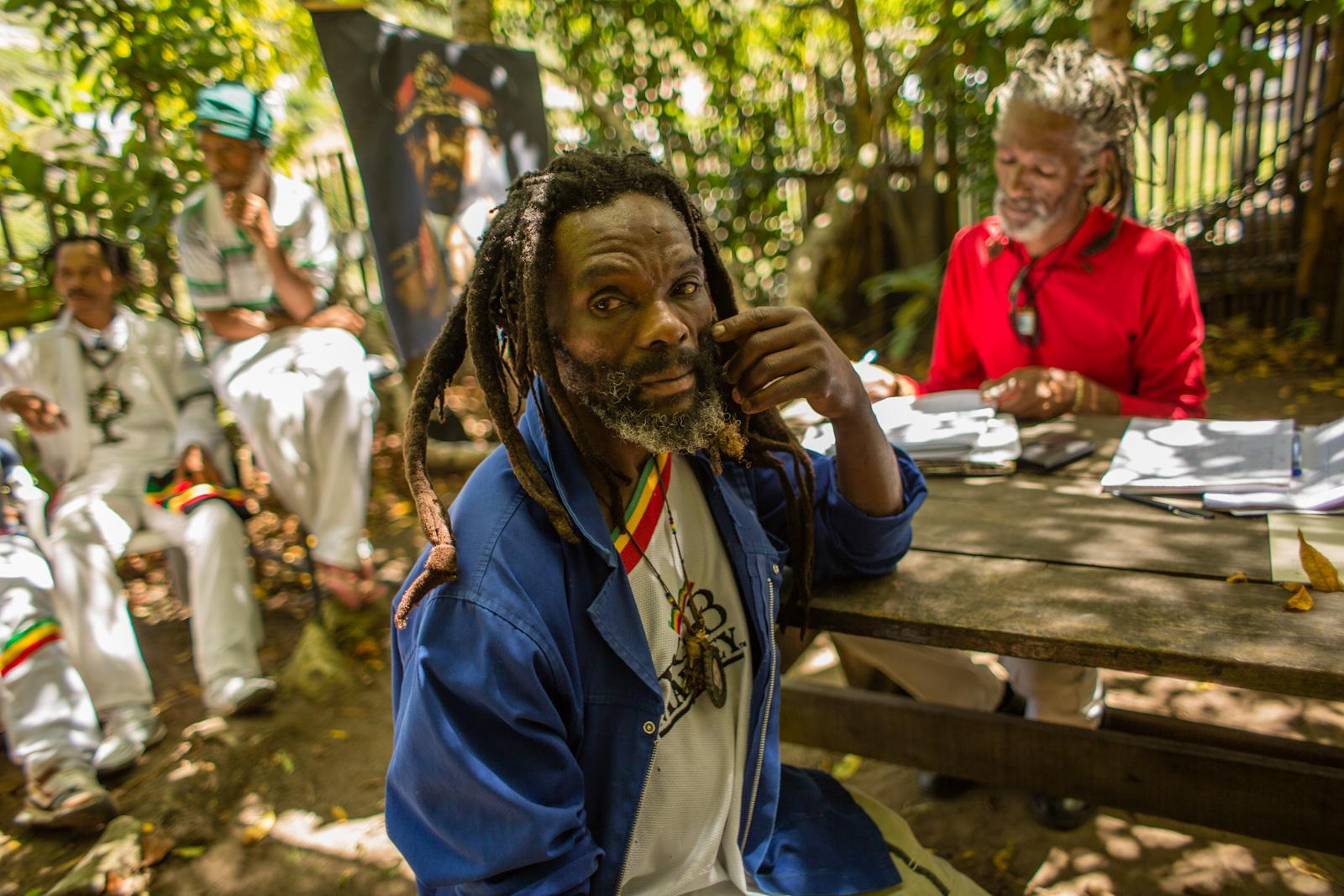 KNYSNA, SOUTH AFRICA - FEBRUARY 07, 2015: Brother Jabu, 50, (C ) and brother Wilfred Jansen, 49, (R ) during the Southern Cape provincial meeting of the three different mansions within Rastafari culture at the Rasta community Judah Square on February 07, 2015 in Knysna, South Africa. The provincial meeting brings together members of the three different Rastafari mansions, which are the 'Nyabinghi', 'Twelve Tribes of Israel' and 'Bobo Shanti', in order to work towards unity and a communal voice as a representation of Rastafari culture and religion. As a religious minority group, the Rastafari movement strives towards the same status as any other religion and a better treatment under the South African government.