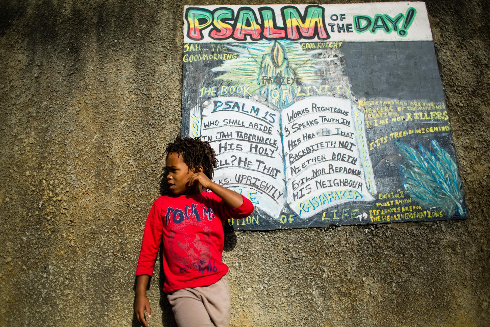 KNYSNA, SOUTH AFRICA - February 05, 2015: Benji in front of the 'Psalm of the Day' panel at Judah Square, Knysna, South Africa on February 05, 2015. In the Rastafari movement, a different psalm is allocated to each day of the year and used as part of the morning praises in the tabernacle at Judah Square.