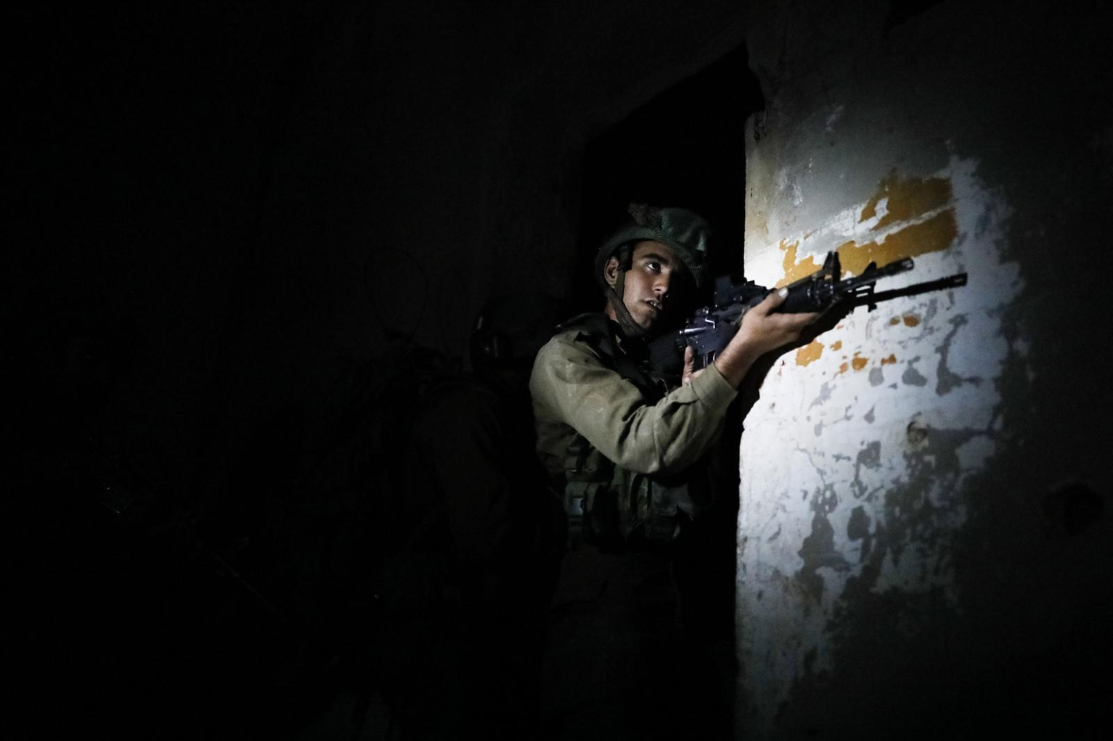 JORDAN VALLEY, ISRAEL - APRIL 05, 2017: An Israeli infantry soldier from the Haruv battalion of the Kfir Brigade takes part in an urban warfare drill that takes place at an abandoned building close to the Kfir Brigade base in the Jordan Valley, West Bank, Israel, on April 05, 2017.