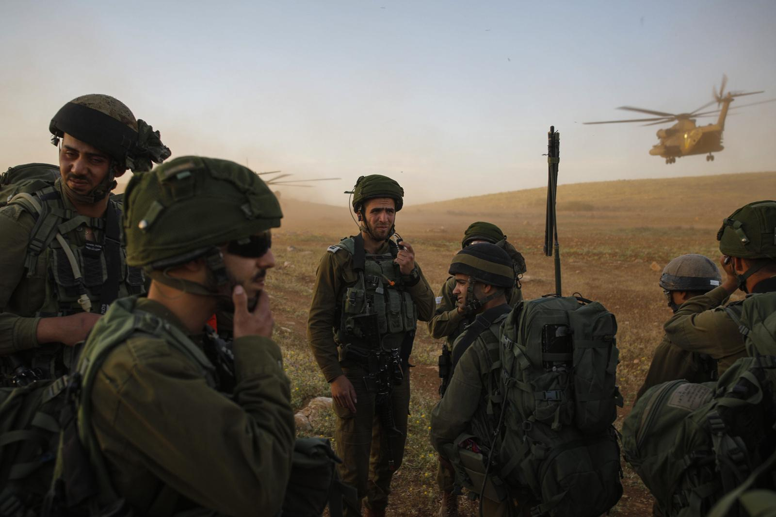 JORDAN VALLEY, ISRAEL - APRIL 05, 2017: Israeli infantry soldiers from the Haruv battalion of the Kfir Brigade take part in a counterterrorism drill with helicopters, that takes place in open fields close to the Kfir Brigade base in the Jordan Valley, West Bank, Israel on April 05, 2017.