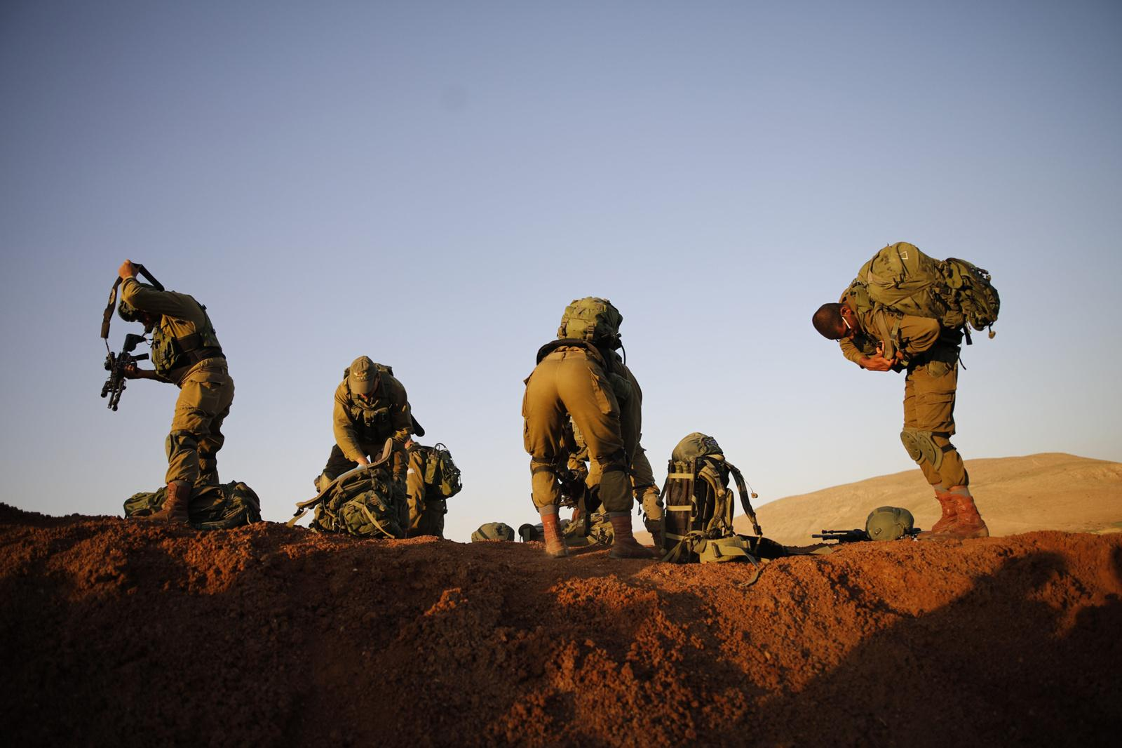 JORDAN VALLEY, ISRAEL - APRIL 05, 2017: Israeli infantry soldiers from the Haruv battalion of the Kfir Brigade prepare themselves for a counterterrorism drill that takes place in open fields close to the Kfir Brigade base in the Jordan Valley, West Bank, Israel, on April 05, 2017.