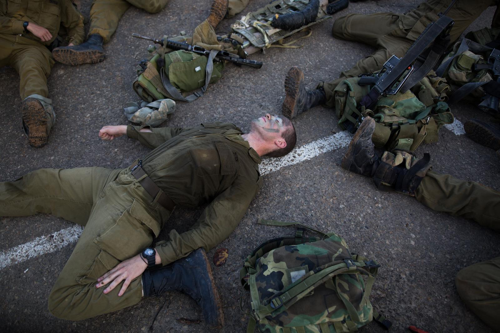 BINYAMINA, ISRAEL - MARCH 08, 2017: Soldiers from the Artillery Corps stretch after taking part in a baret march at the end of their basic army training on March 08, 2017, near the Northern town of Binyamina, Israel. Around 600 soldiers participated in the march of around 25km, that lasted from midnight until the early morning hours.
