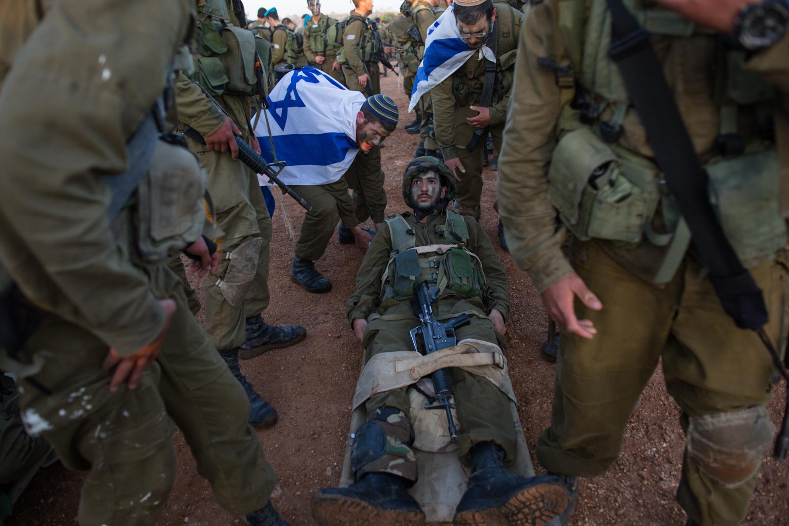 BINYAMINA, ISRAEL - MARCH 08, 2017: Soldiers from the Artillery Corps place their comrade on a stretcher while taking part in a baret march at the end of their basic army training on March 08, 2017, near the Northern town of Binyamina, Israel. Around 600 soldiers participated in the march of around 25km, that lasted from midnight until the early morning hours.