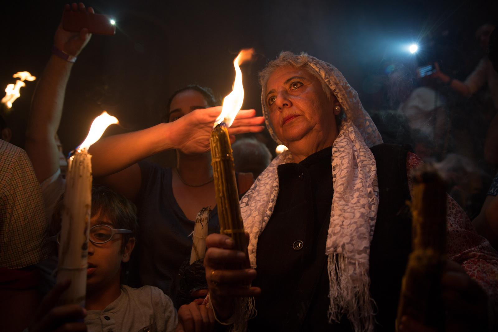 JERUSALEM, ISRAEL - APRIL 30, 2016: Orthodox Christian worshippers light packs of candles as they take part in the Holy Fire ceremony at the Church of the Holy Sepulchre, traditionally believed to be the burial site of Jesus Christ, in Jerusalem's Old City during the Easter holiday, April 30, 2016.