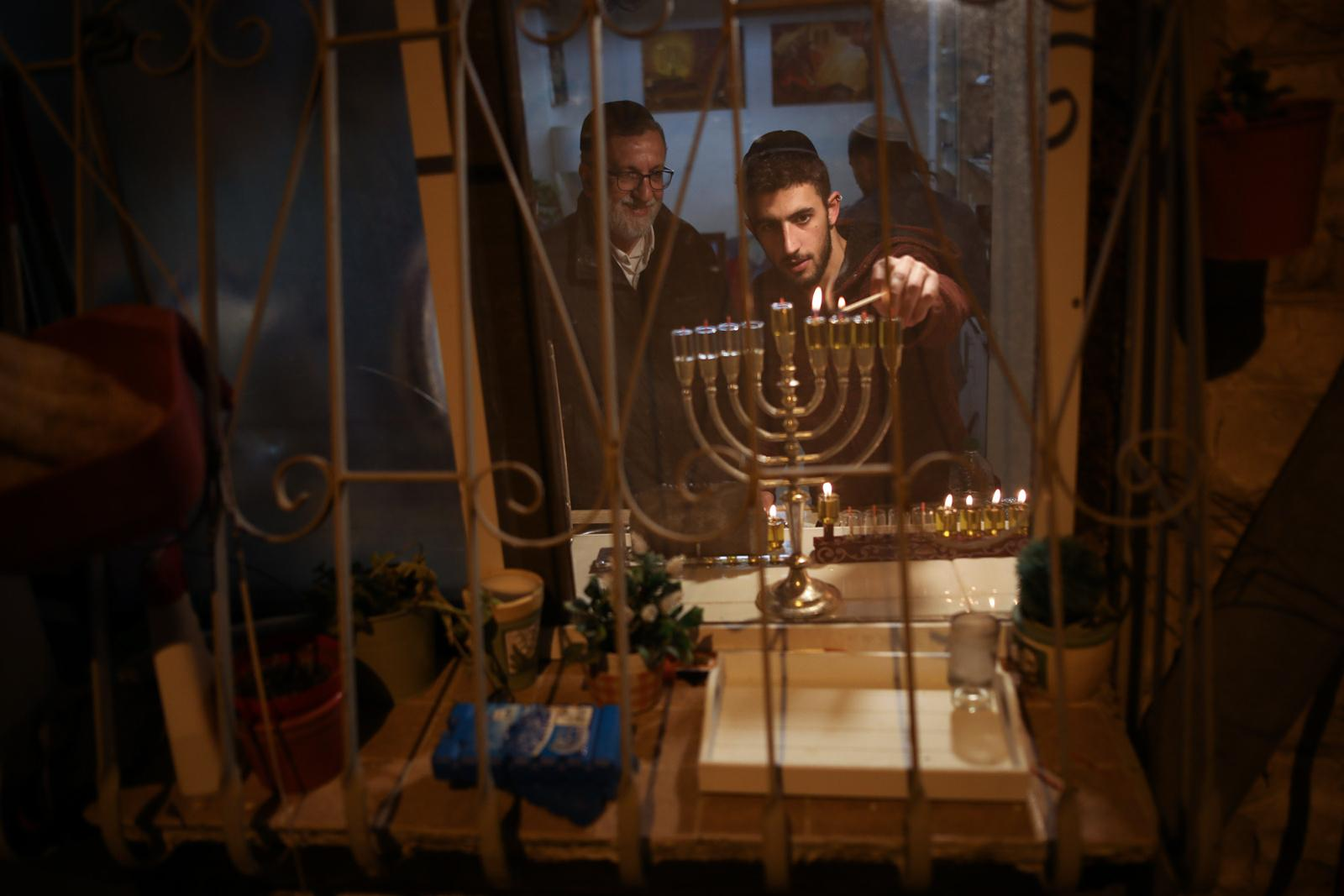 An young Jewish man lights candles at his home on the fourth night of the holiday of Hanukkah in Jerusalem's Nachlaot neighourhood, Israel, December 05, 2018