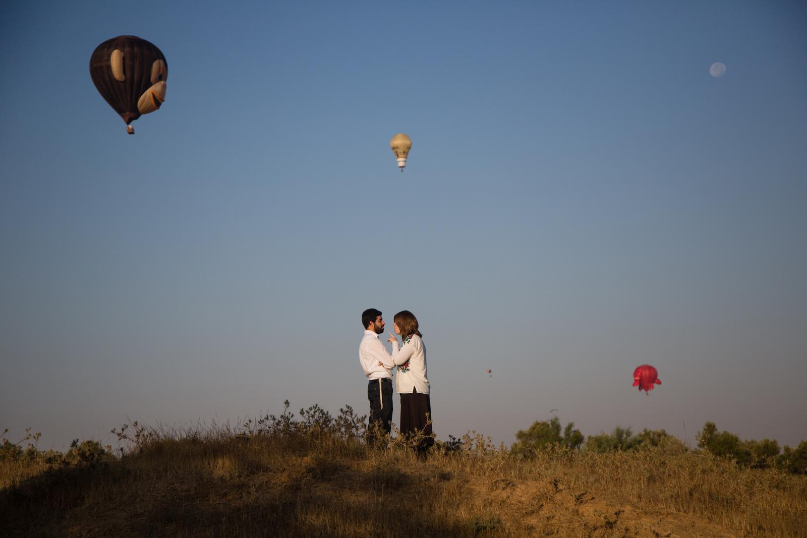 An Ultra-Orthodox Jewish couple stand together as hot air balloons fly overhead during a two-day international hot air balloon festival in Eshkol Park near the southern city of Netivot, Israel July 22, 2016.