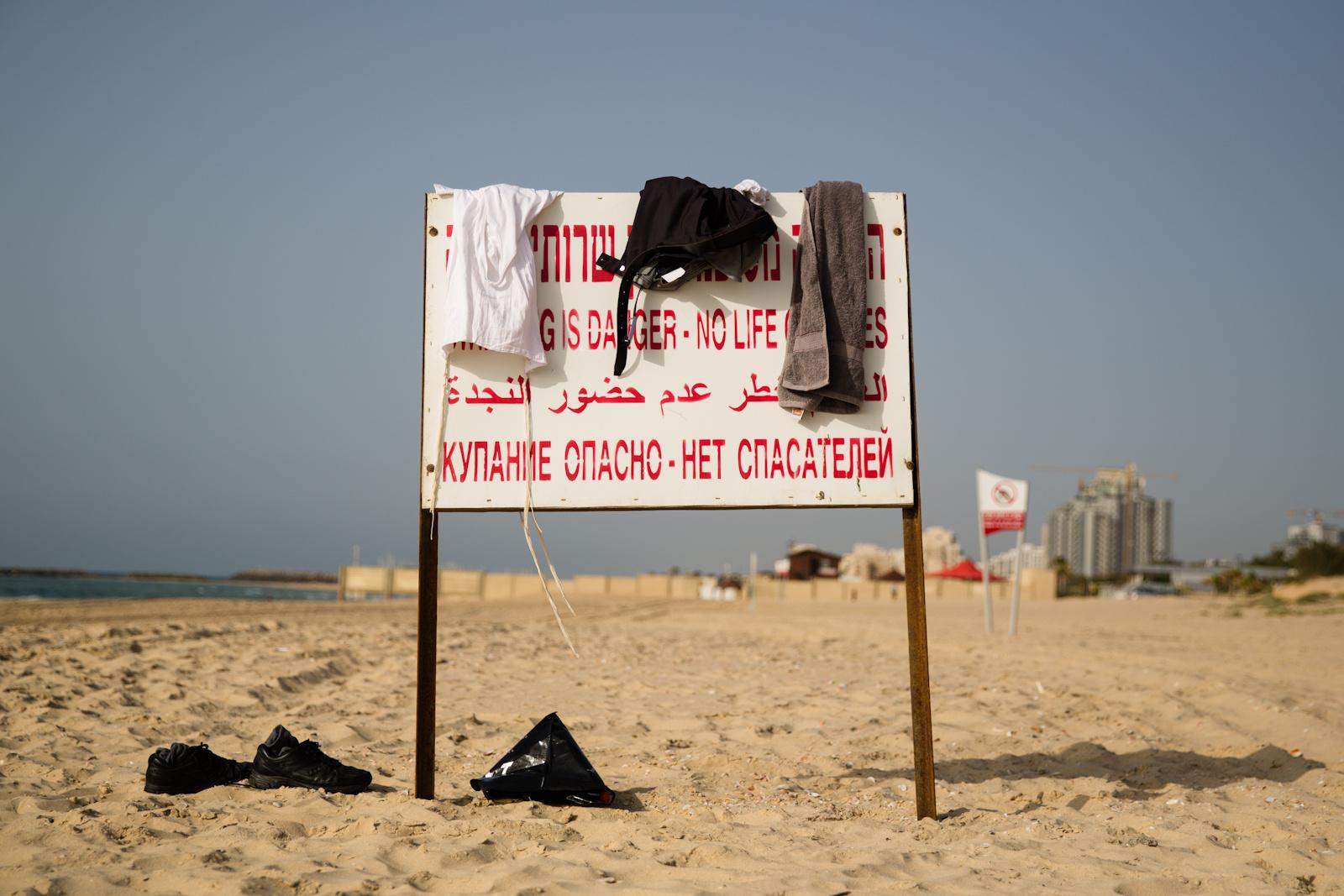 "ASHKELON, ISRAEL - APRIL 24, 2016: The clothes of Ultra Orthodox jewish men hang on a sign reading ""swimming is danger - no lifeguards"" on the beach in Ashkelon, April 6, 2016."