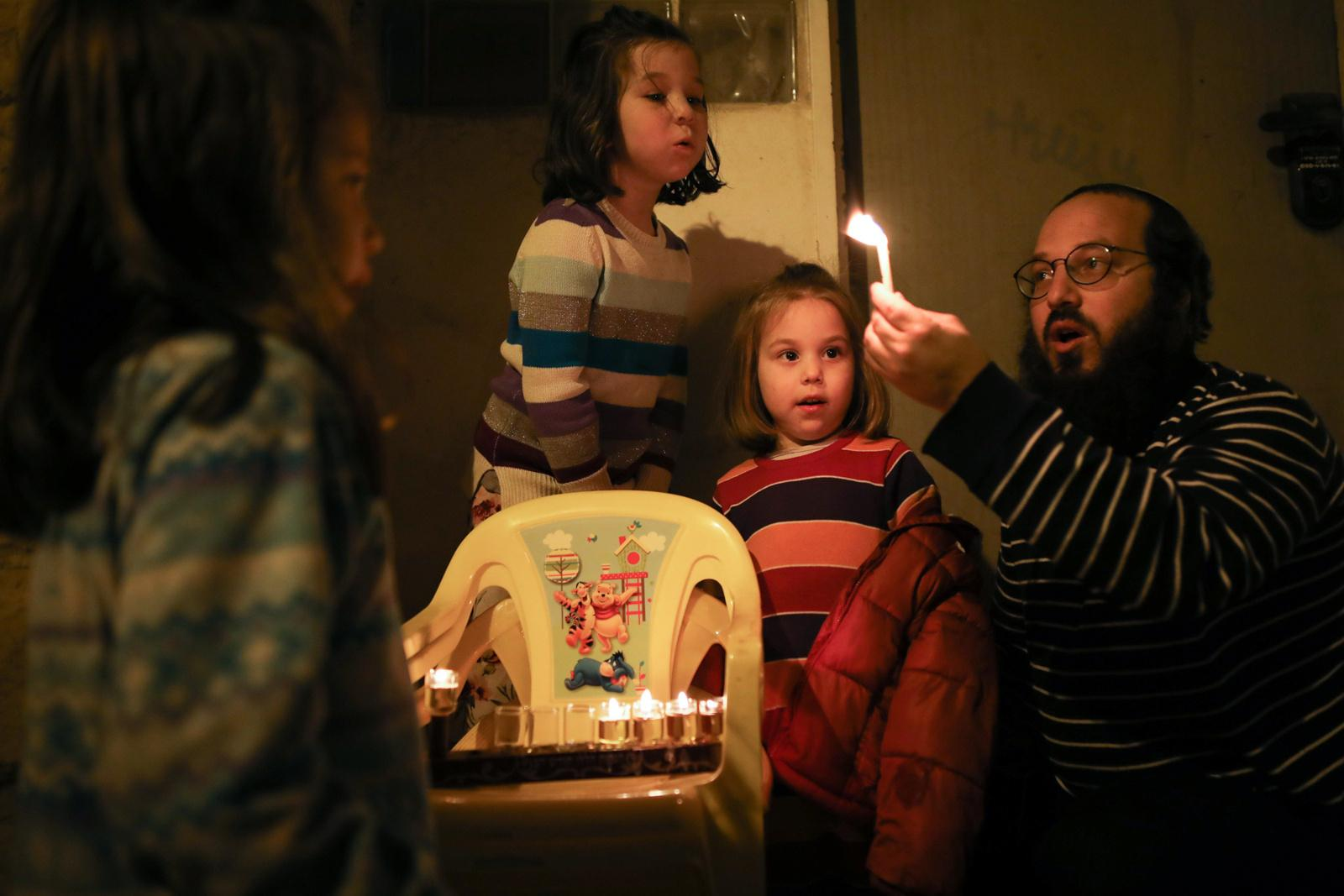 An ultra-orthodox Jewish family lights candles at their home on the fourth night of the holiday of Hanukkah in Jerusalem's Nachlaot neighourhood, Israel, December 05, 2018